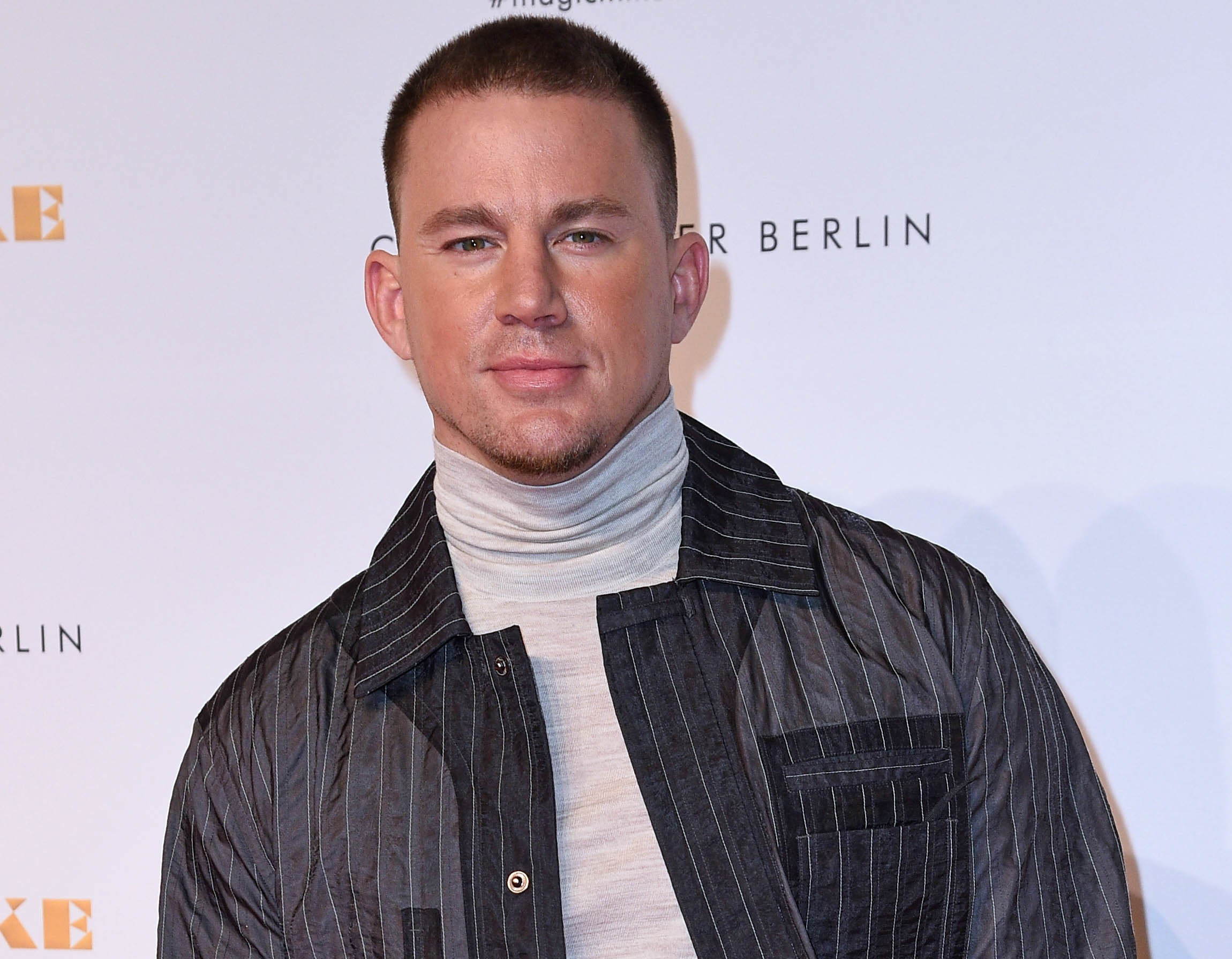 Channing wears a grey turtleneck shirt and pinstripe jacket