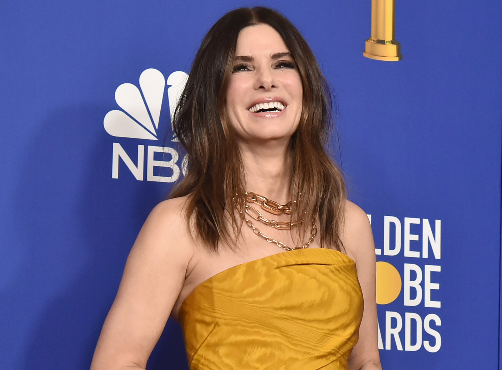 Sandra smiles while wearing a strapless golden colored dress
