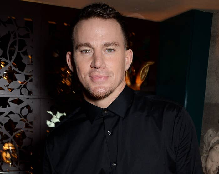Channing softly smiles while wearing a black button down at an event