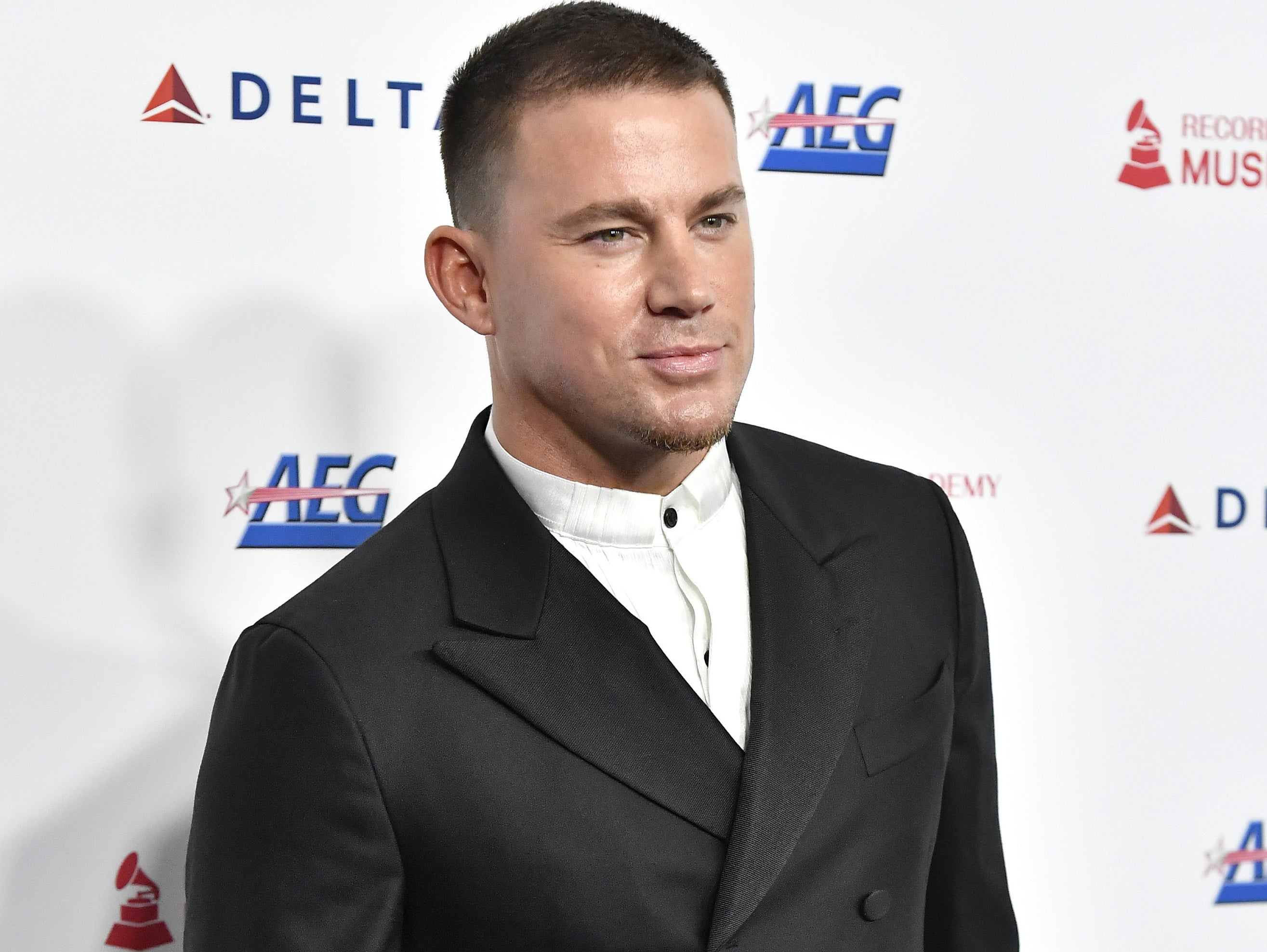 Channing wears a white button down and black blazer