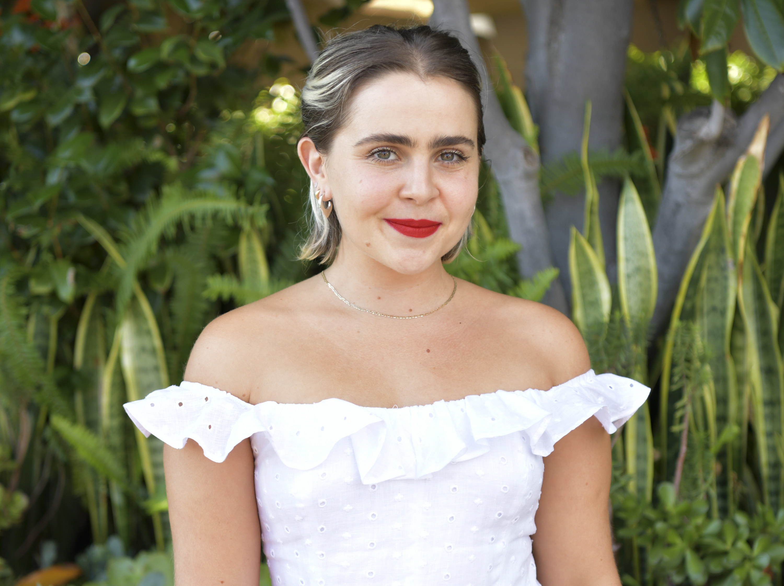 Mae wears a white off the shoulder eyelet top