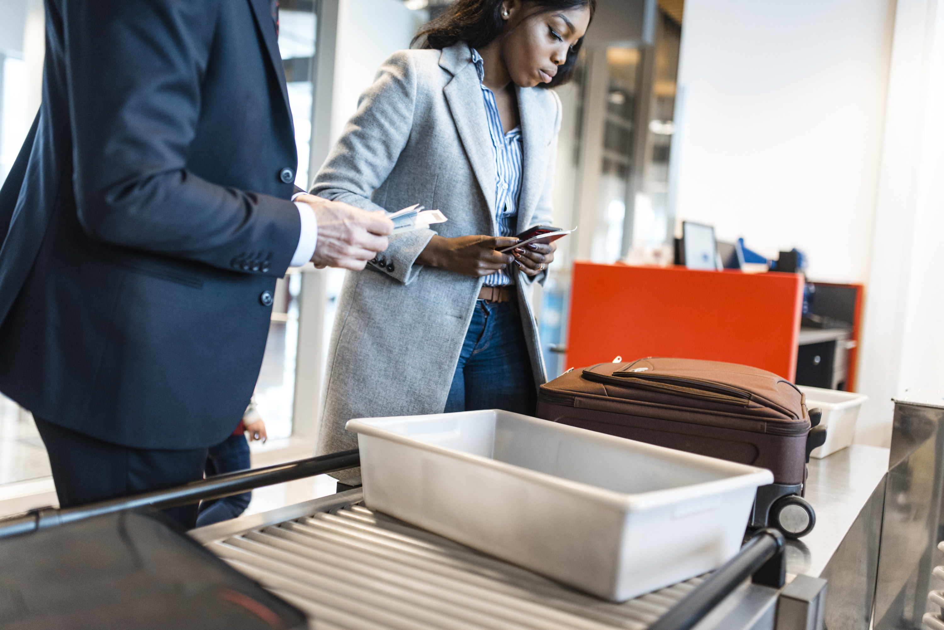Two people putting their items in bins for airport security