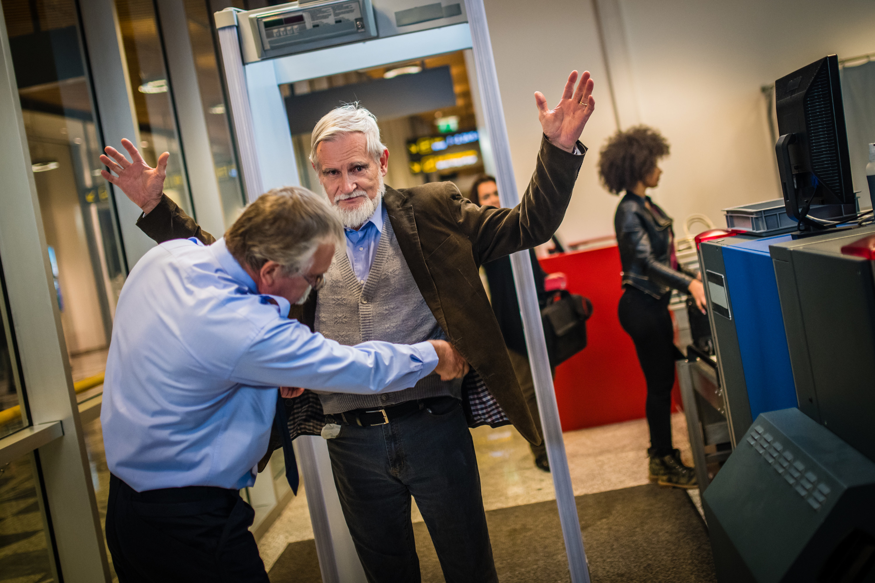 Man at airport getting patted down by airport secuirty