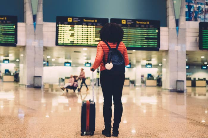 Woman looks at departure screens with her suitcase