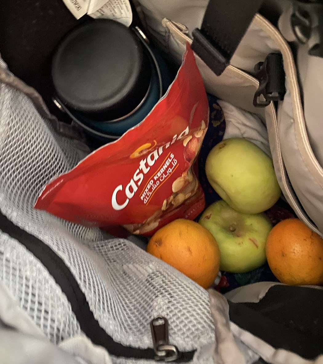 Backpack with a water bottle, nuts, and fruit