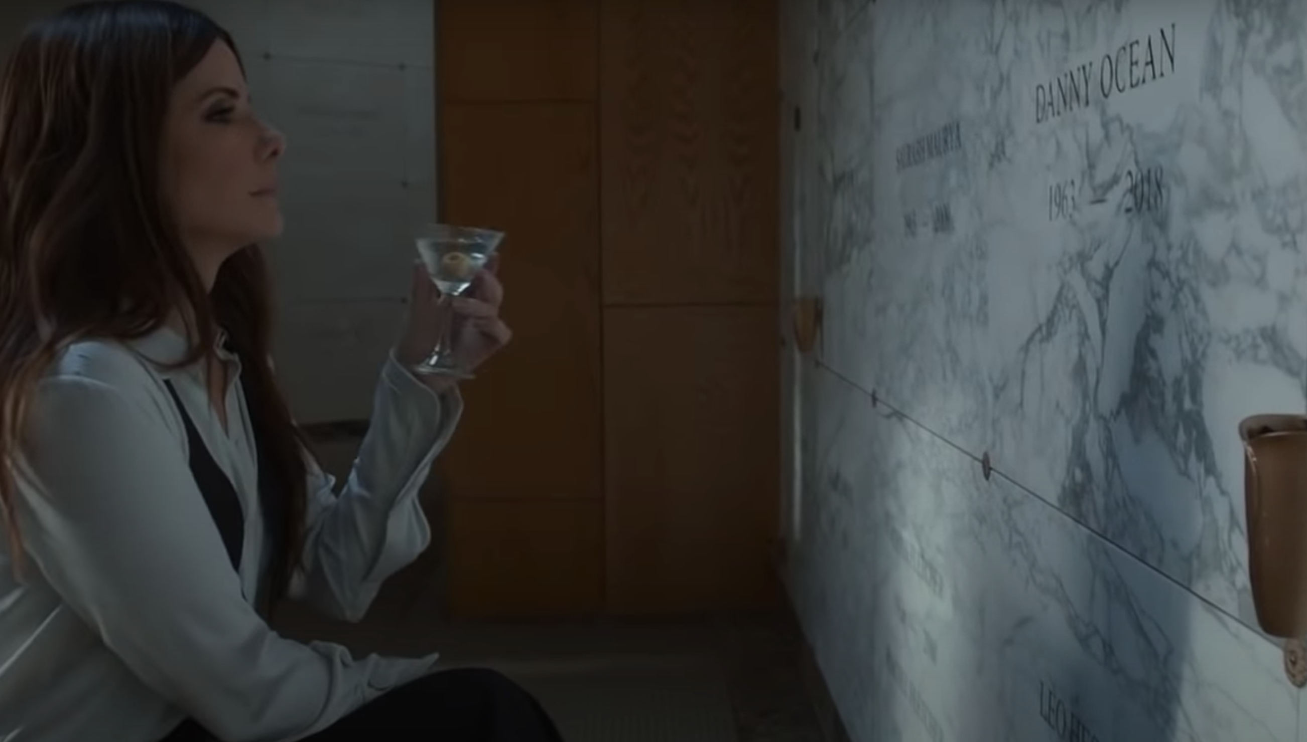 Debbie drinking a martini next to Danny's grave