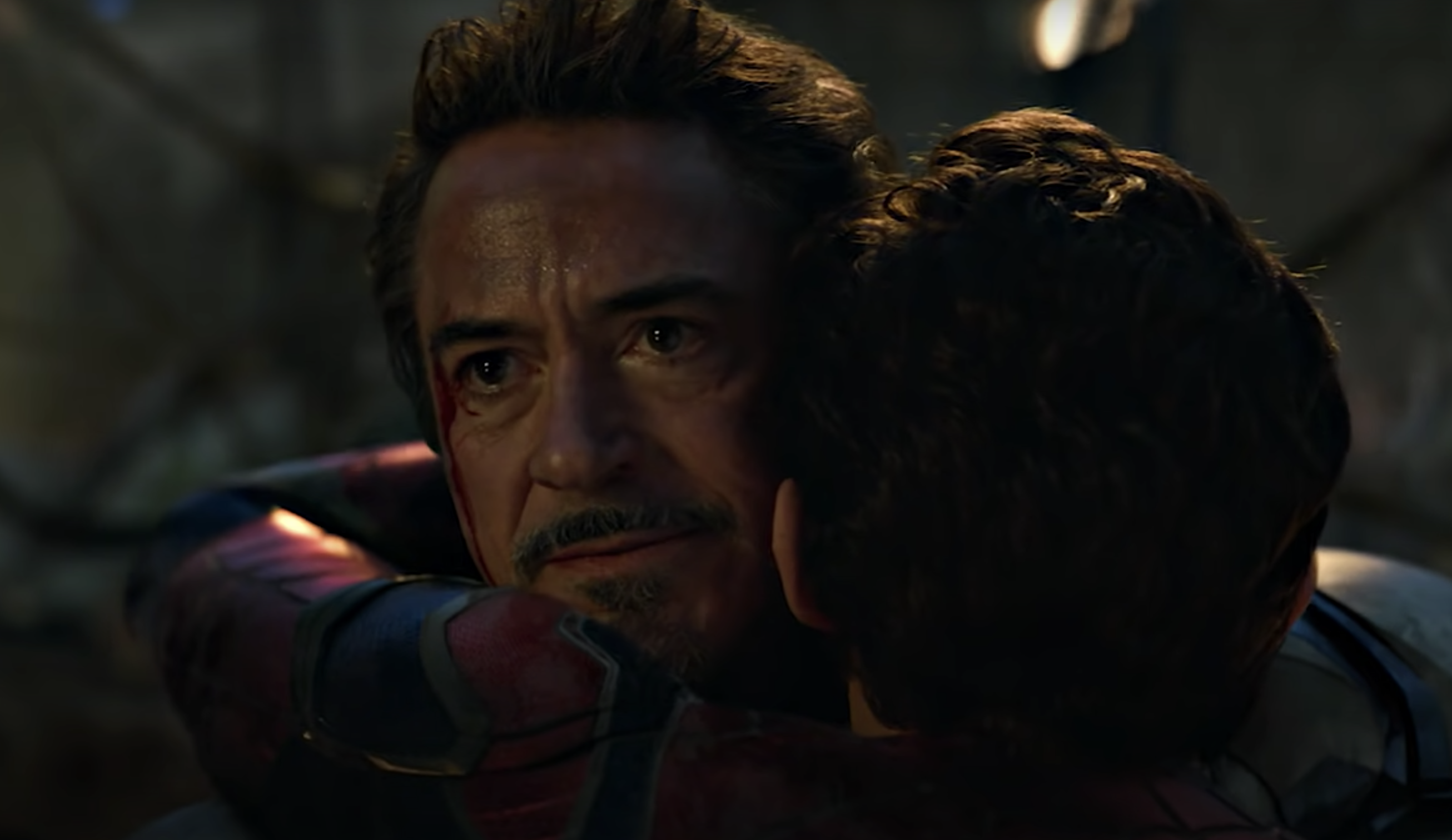 Tony Stark hugging Peter in the middle of the battle