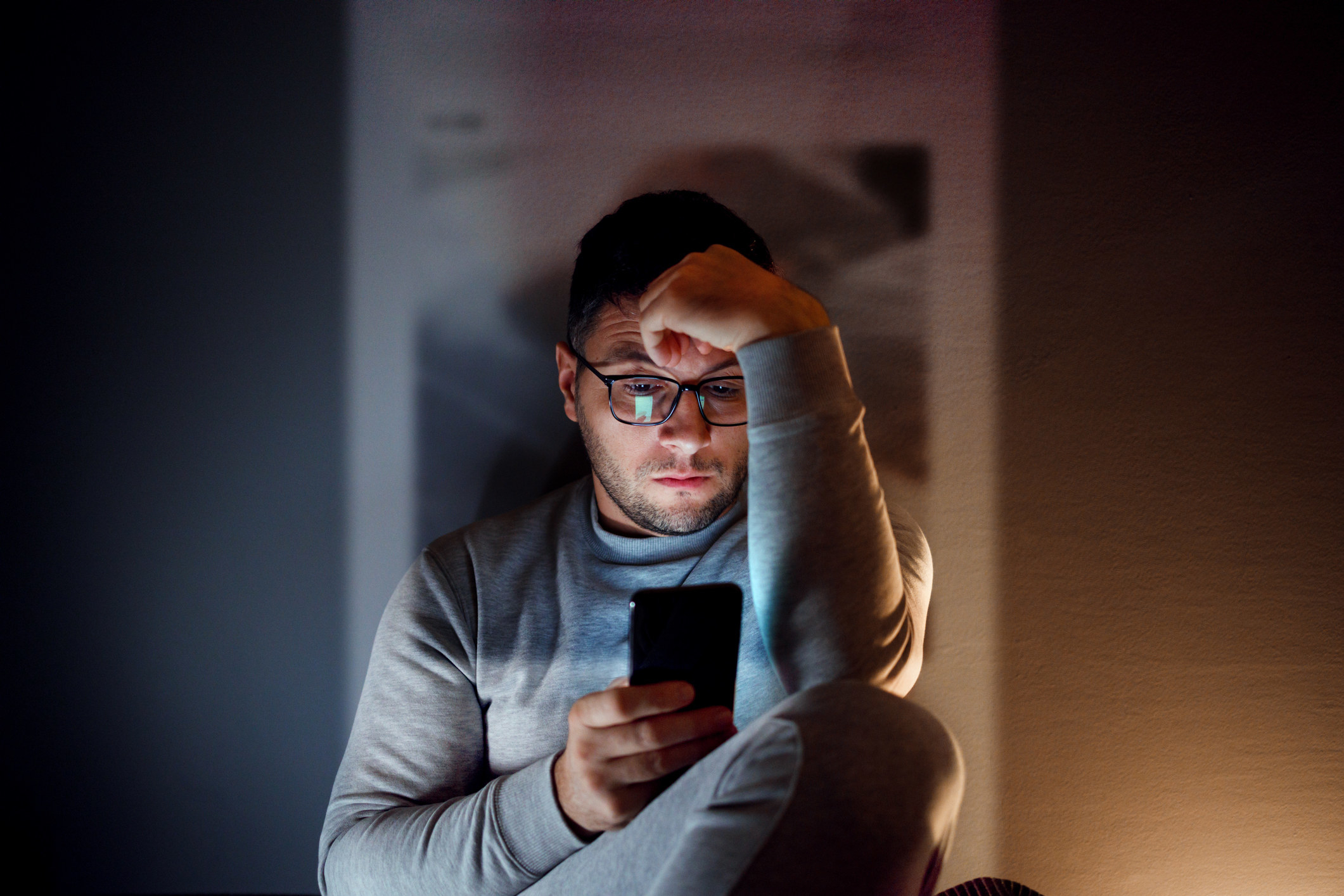 Person looking at their phone in a dark room and feeling bad about themself