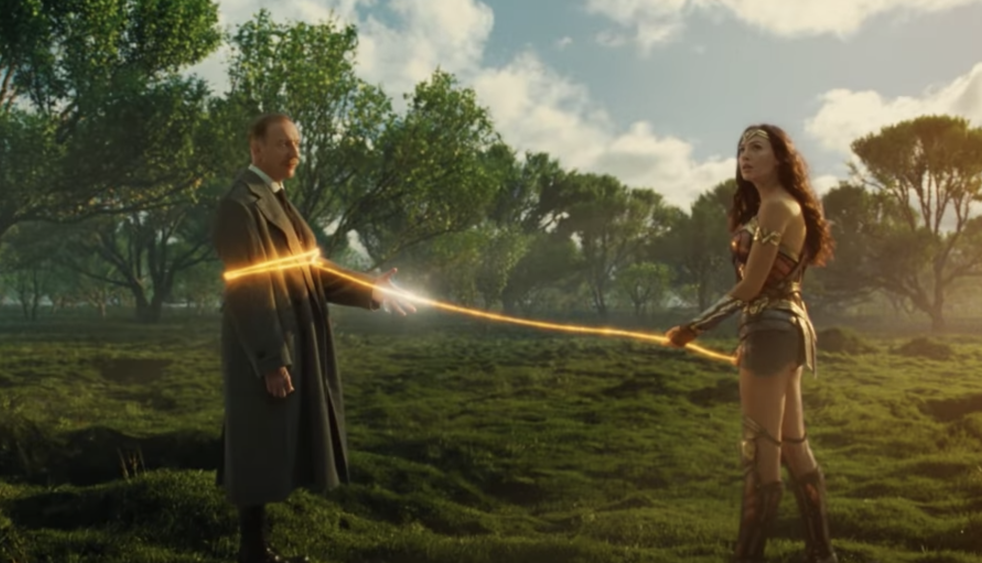 Wonder Woman with her lasso around Ares in a field