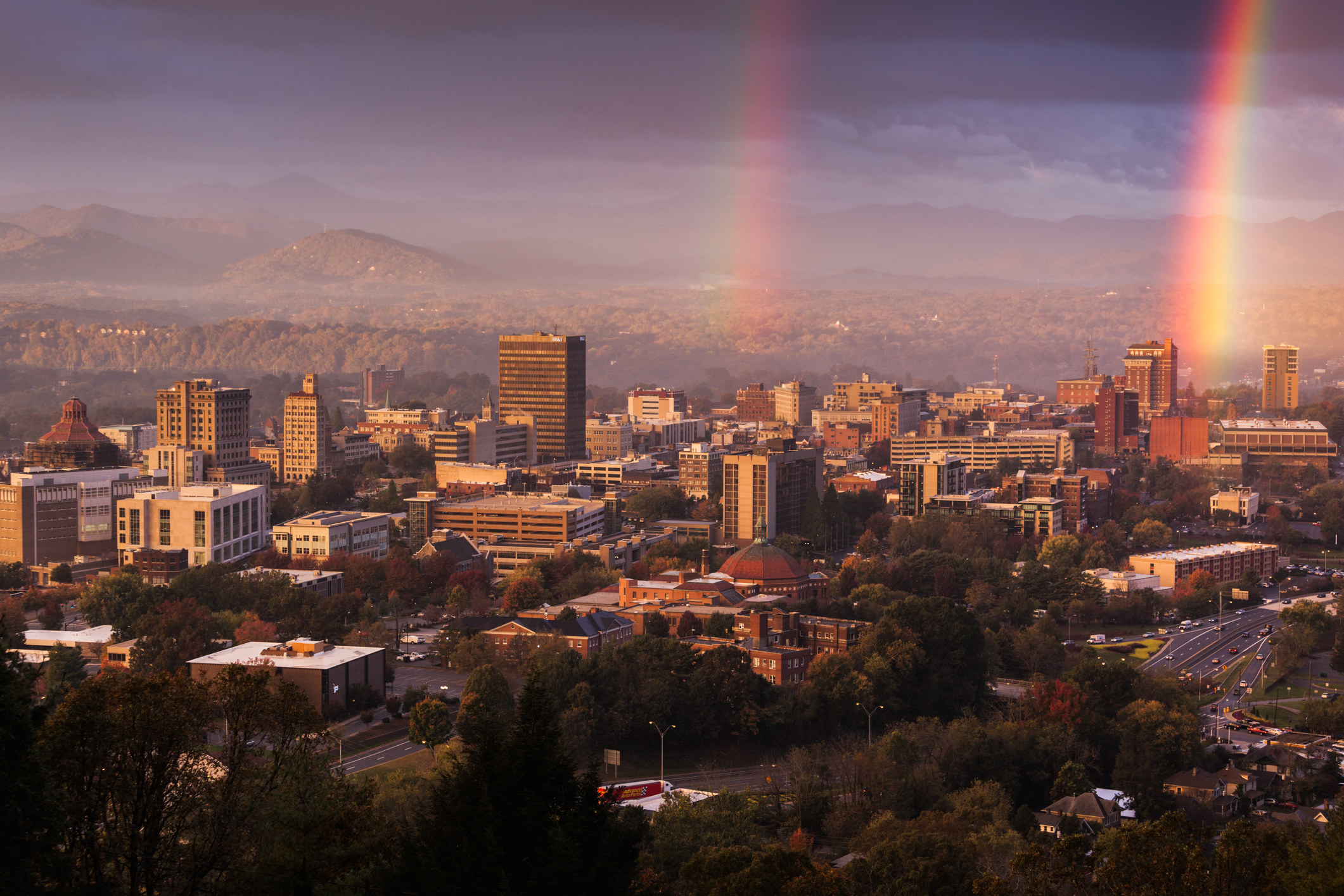 The Asheville skyline with mountains in the background and rainbows.