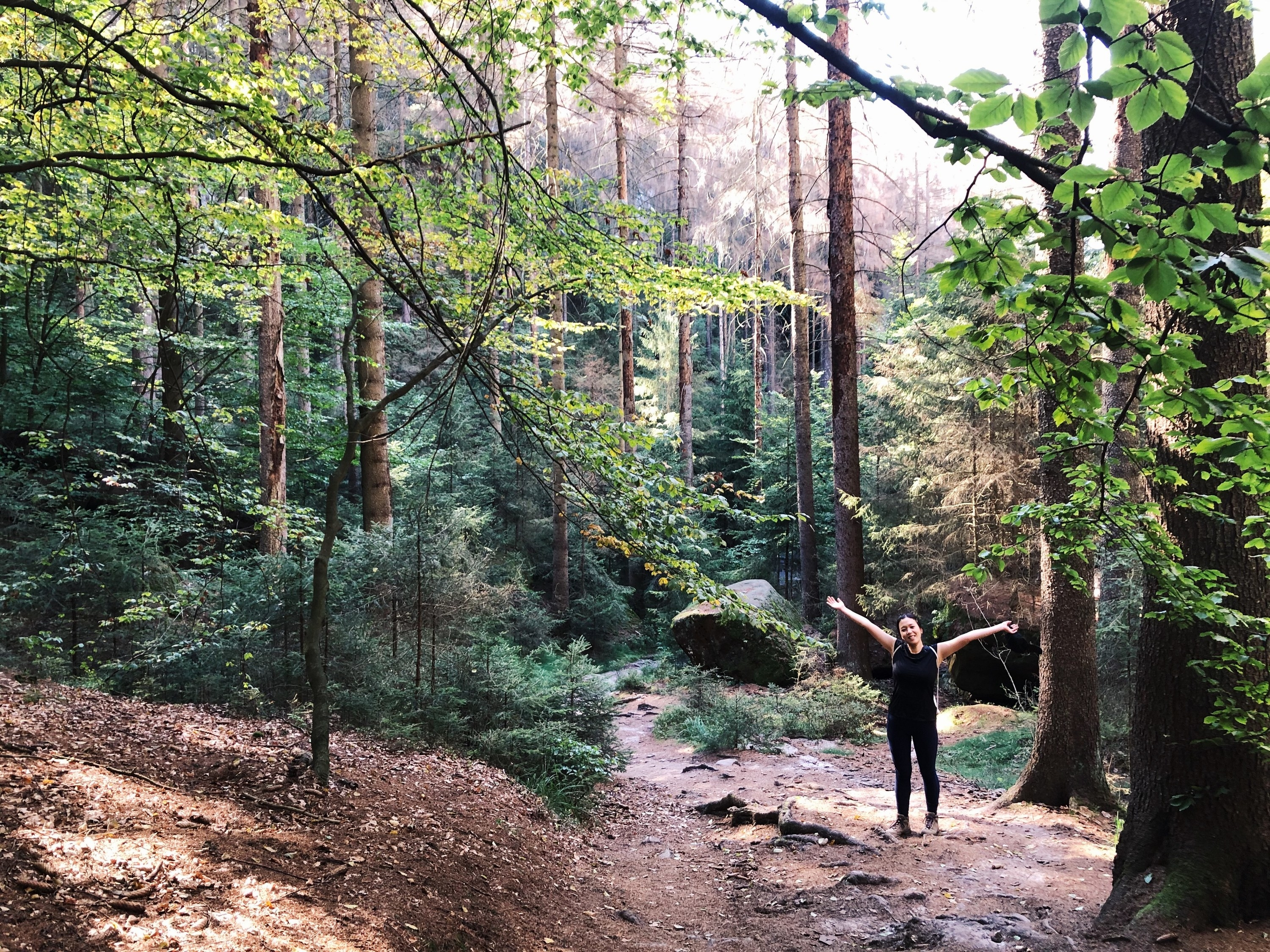 The writer holding her hands out in the middle of a verdant Berlin forest