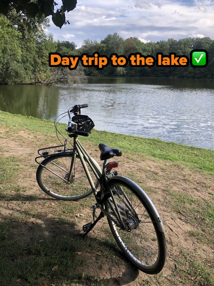 """Writer's bike parked right next to a lake, with text reading, """"Day trip to the lake, check"""""""