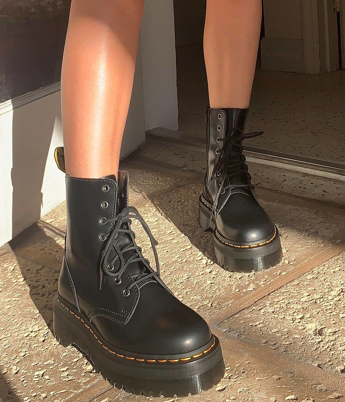 a person wearing a pair of dr. marten platform boots