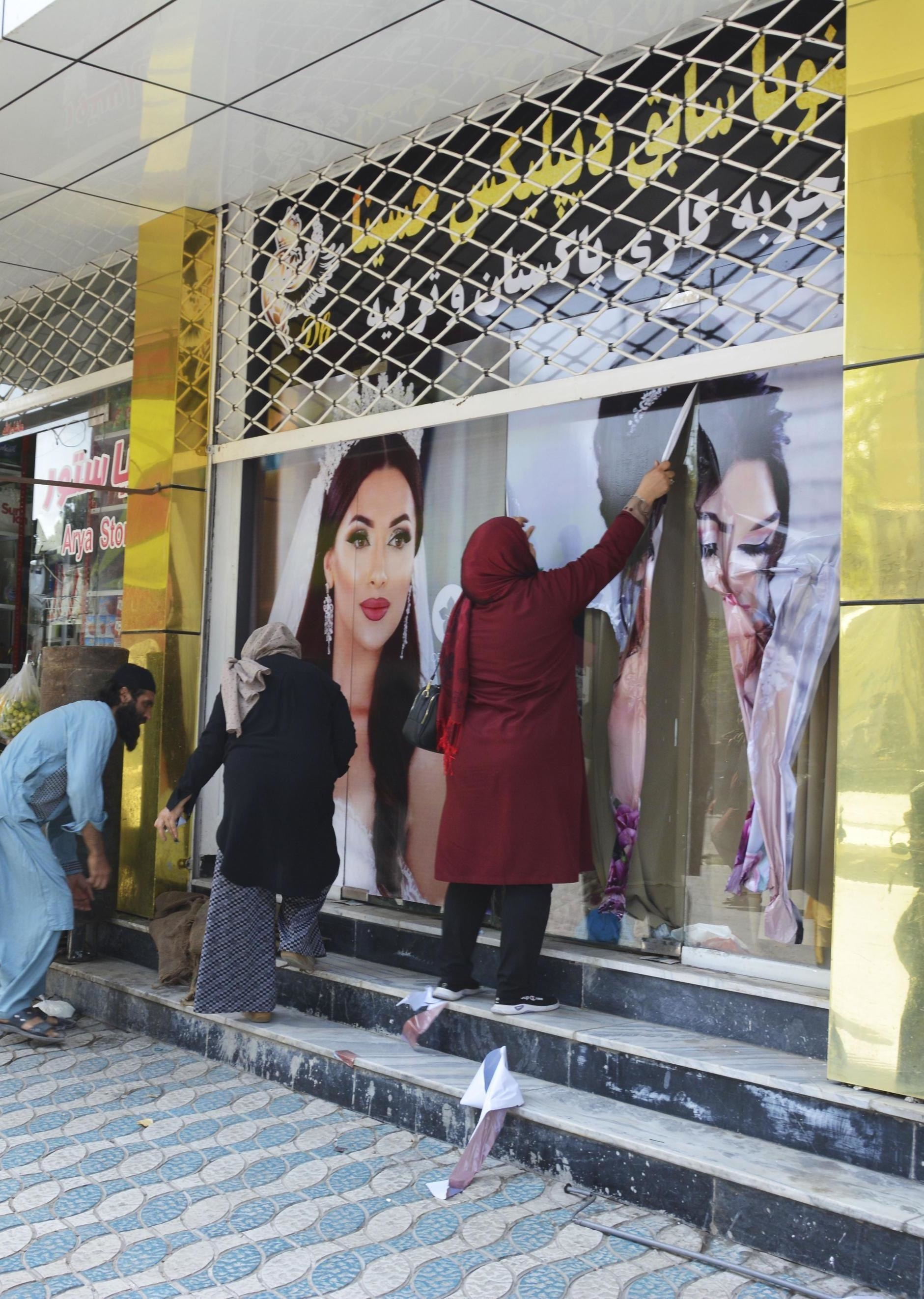 Workers at a beauty salon strip large photos of women off the wall in Kabul