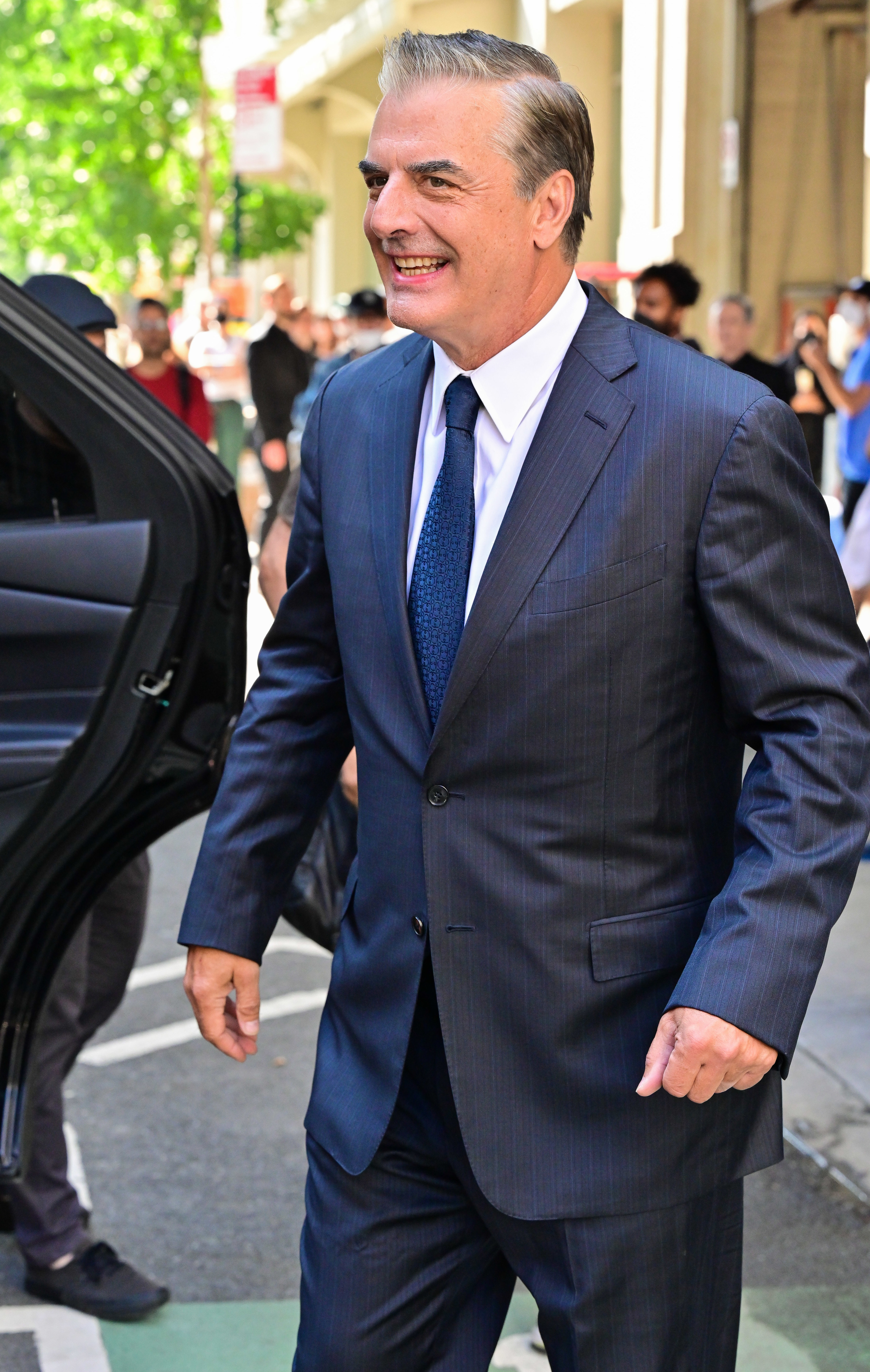 Chris Noth is pictured smiling on the set of And Just Like That...