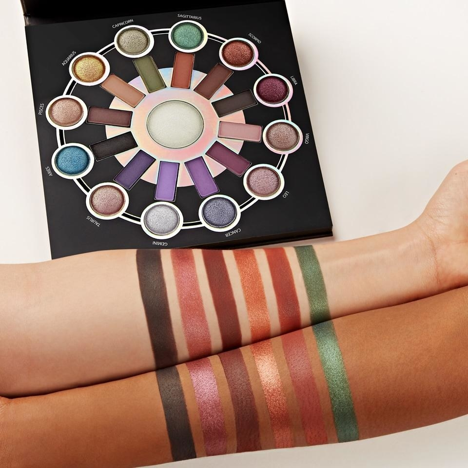 two arms with swatches of makeup in front of the palette with a color for each horoscope sign