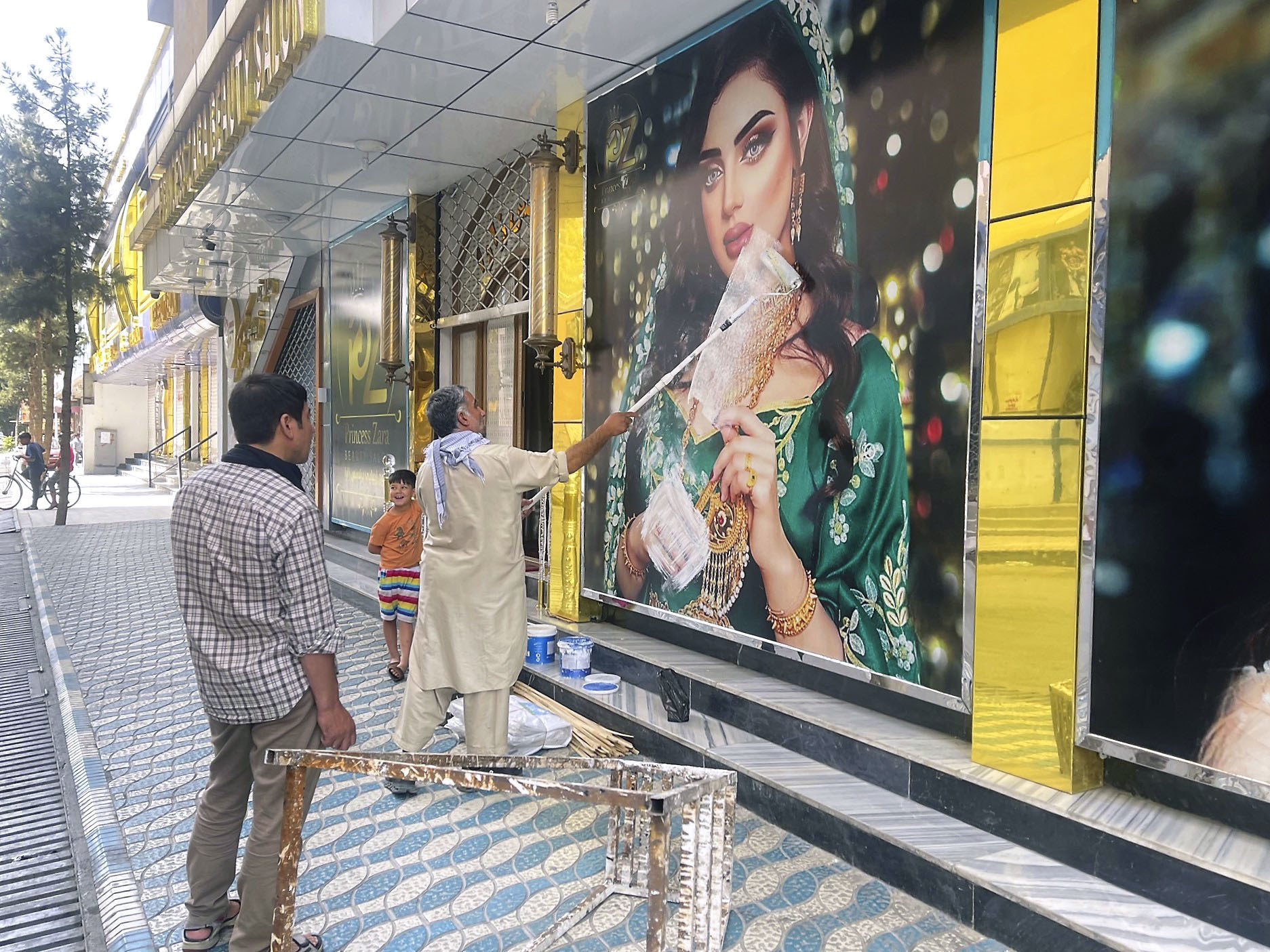 A worker at a beauty salon paints over a large photo of a woman on the wall in Kabul following news that the Taliban swept into the Afghan capital