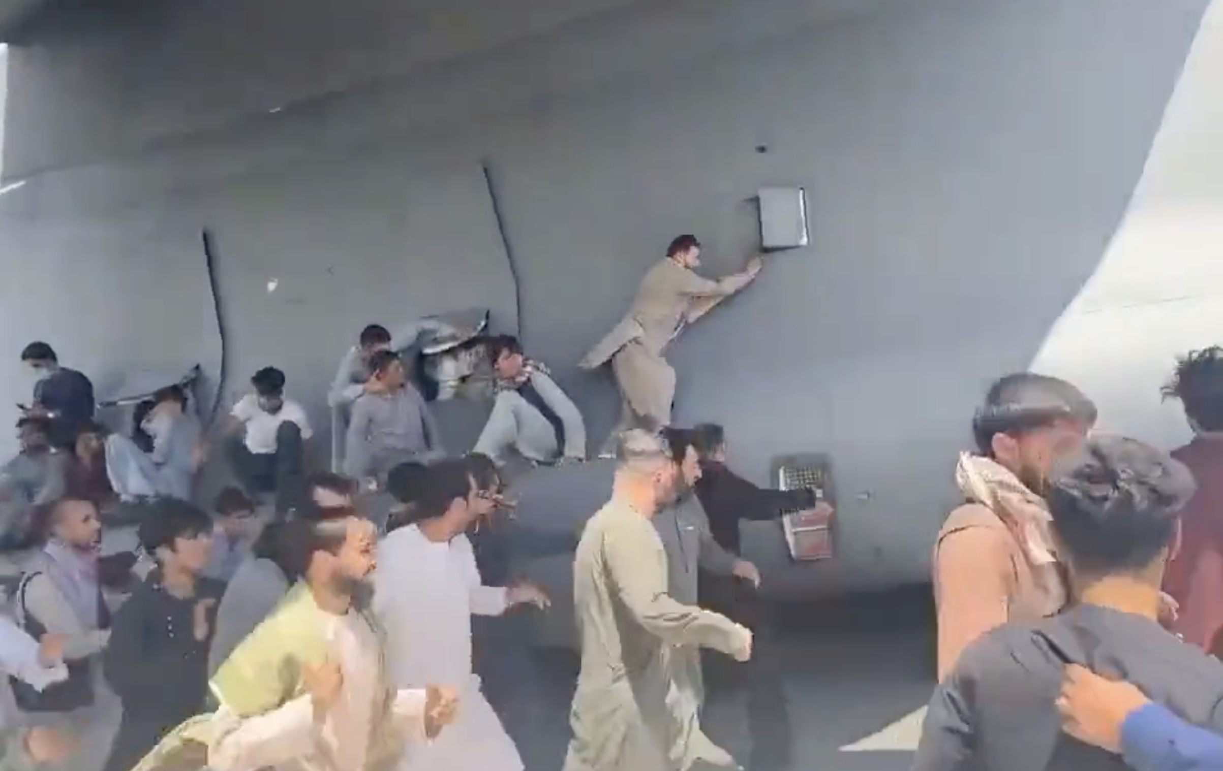 People hang onto US military aircraft as it attempts to take off