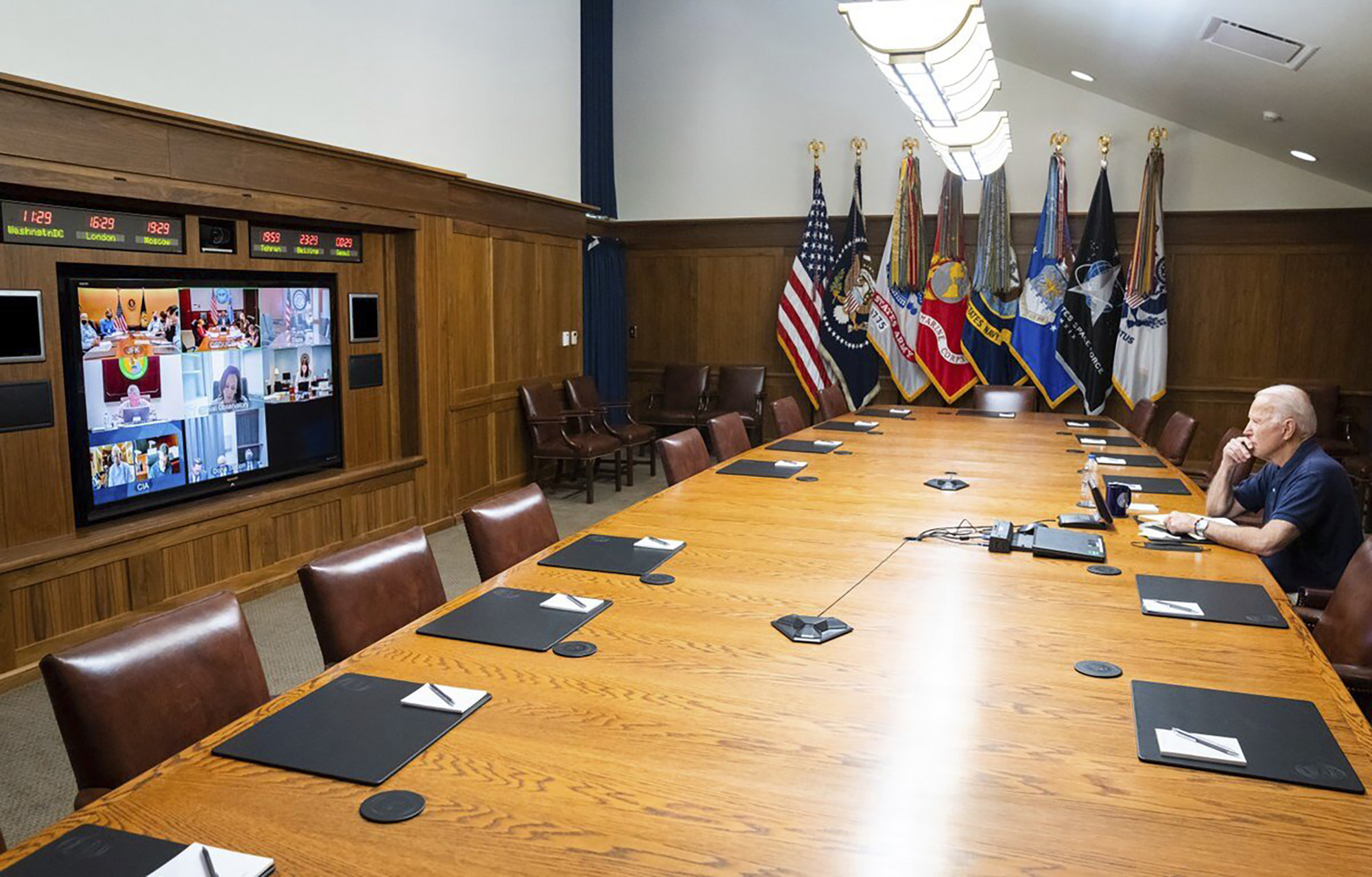 President Joe Biden sitting alone at a table at Camp David as he virtually met with his national security team and senior officials for a briefing on Afghanistan