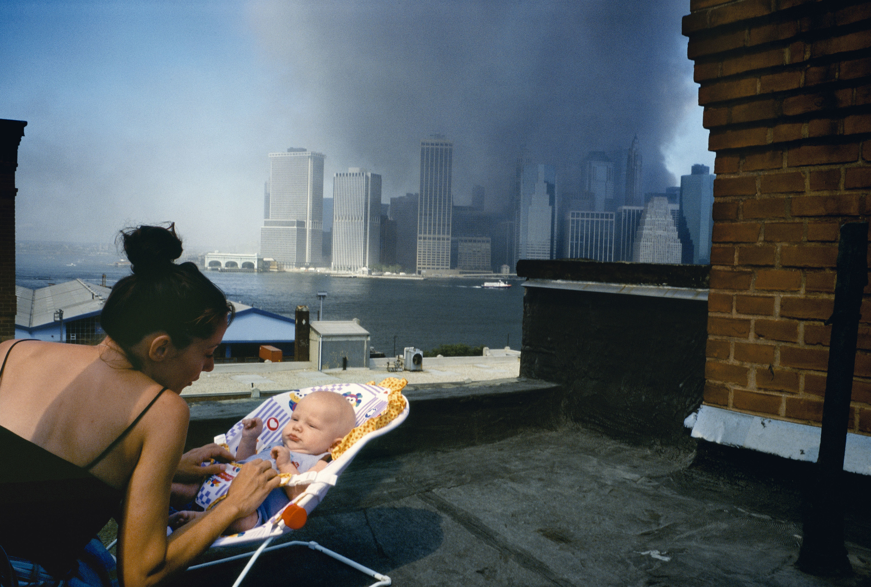 A woman with a baby on the roof overlooking the New York skyline, which is obscured with smoke from the towers