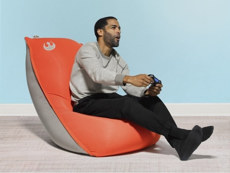 model lounging on the bean bag while playing video games. there is a rebel logo in the top corner.