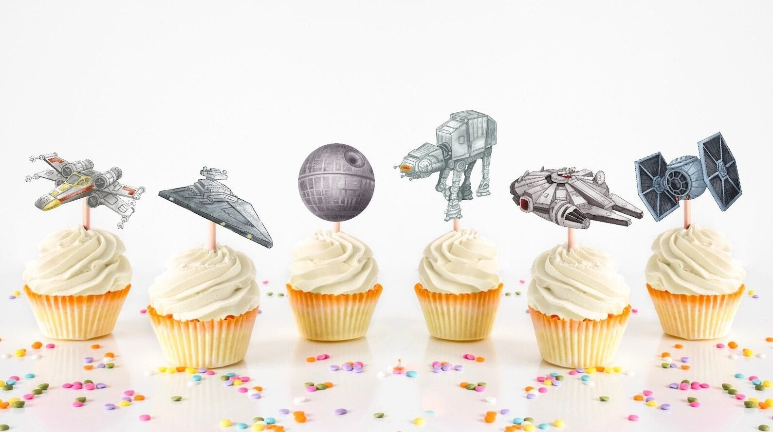 cupcakes with watercolor toppers featuring several different ships and machines in star wars