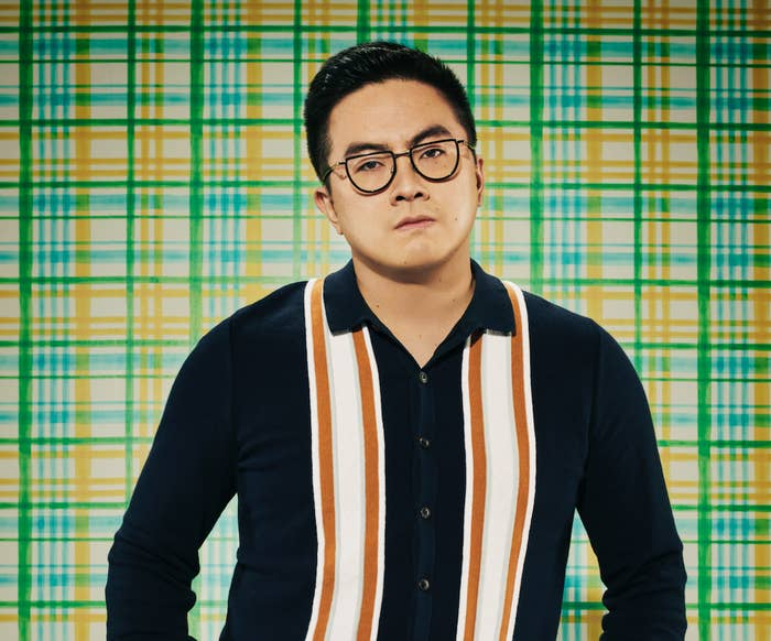 Bowen Yang looking serious against a checkered background