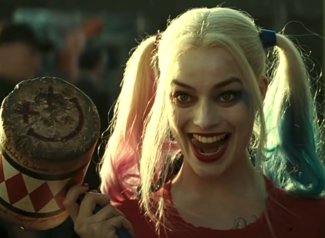 """Margot Robbie in """"Suicide Squad"""" holding a mallet with a mischievous look on her face"""