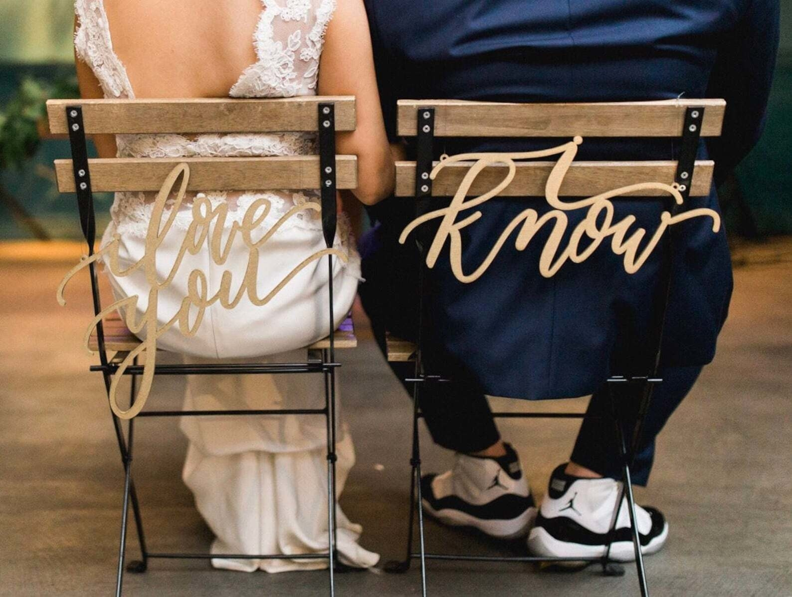 couple sitting side by side. the back of one chair has a sign that reads i love you and the other sign says i know