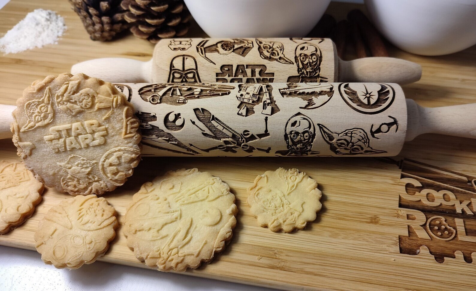 two rolling pins beside several baked sugar cookies with imprints from the pins