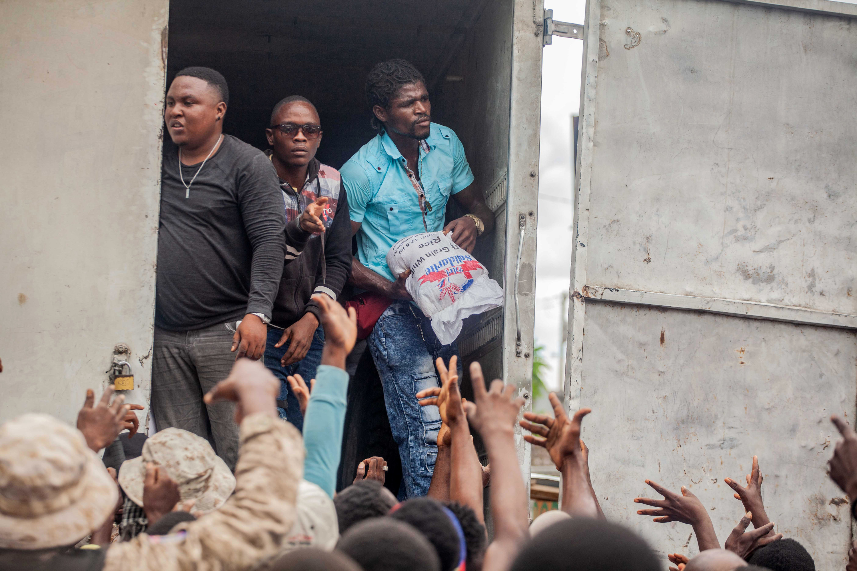 Arms from a crowd of Haiti residents reach up toward a man carrying a bag of rice