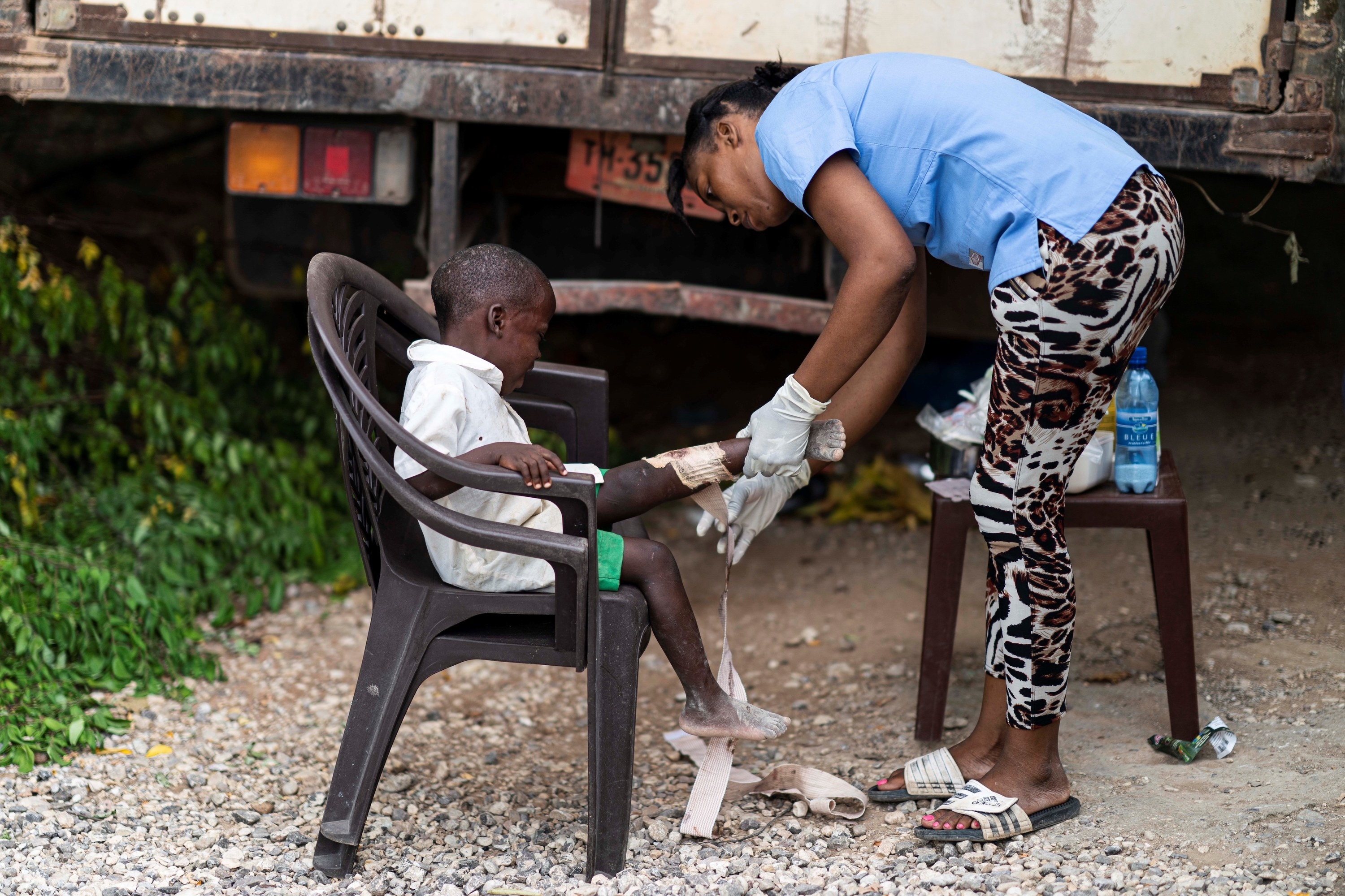A young Haitian child cries while a medical worker wraps their leg with gauze