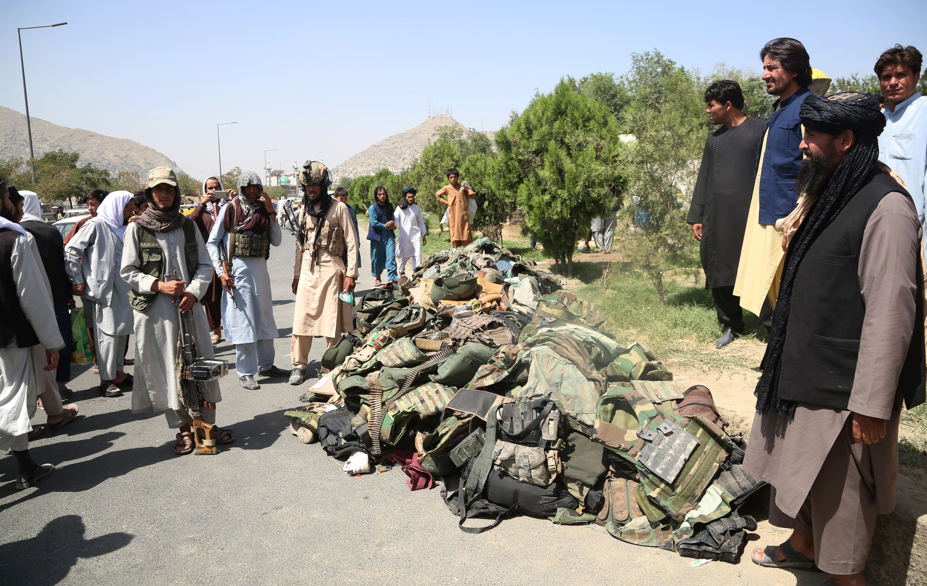 Taliban fighters stand beside the belongings of Afghan security soldiers in Kabul