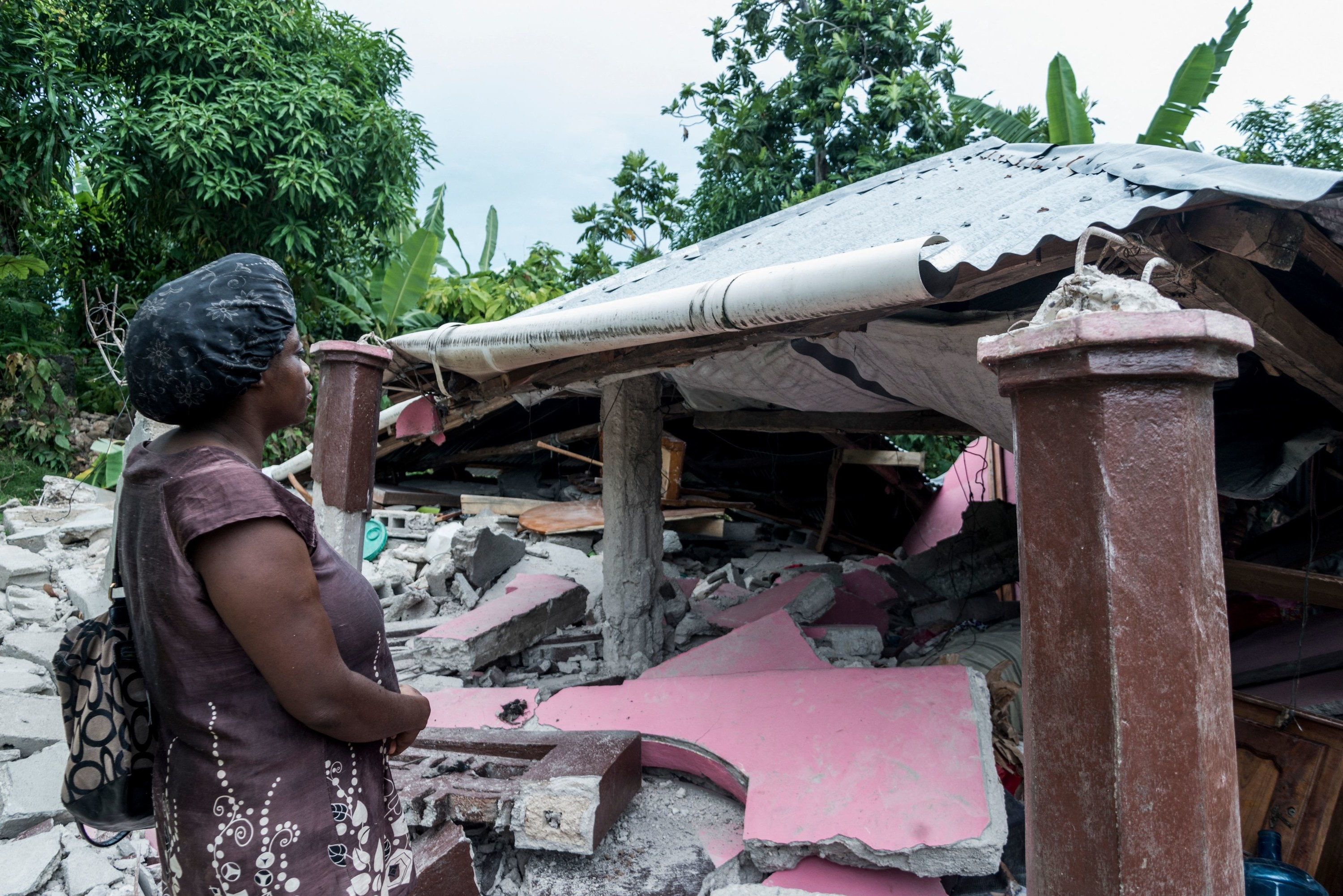 A Haitian woman faces concrete rubble and a collapsed roof