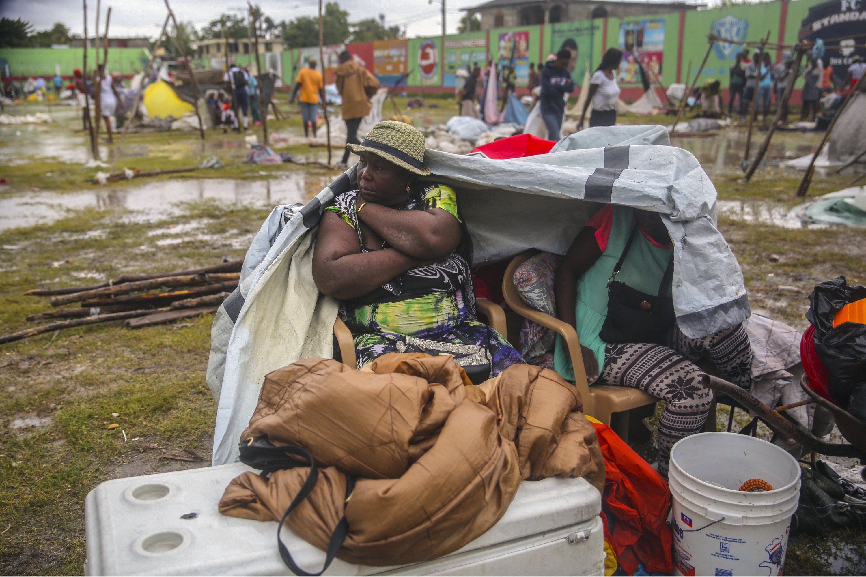 A woman sits outside under a tarp, surrounded by belongings as it rains
