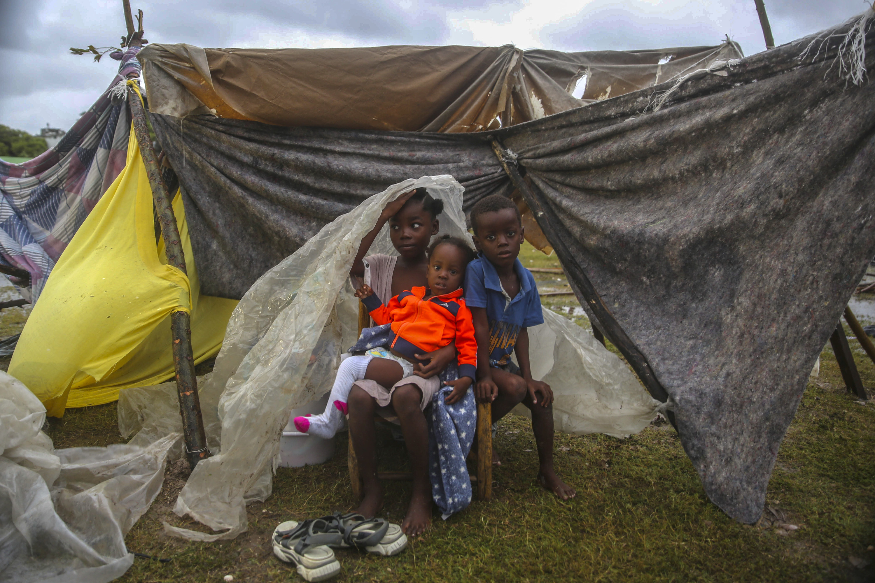 Three young children, one a toddler, huddle together under a tent