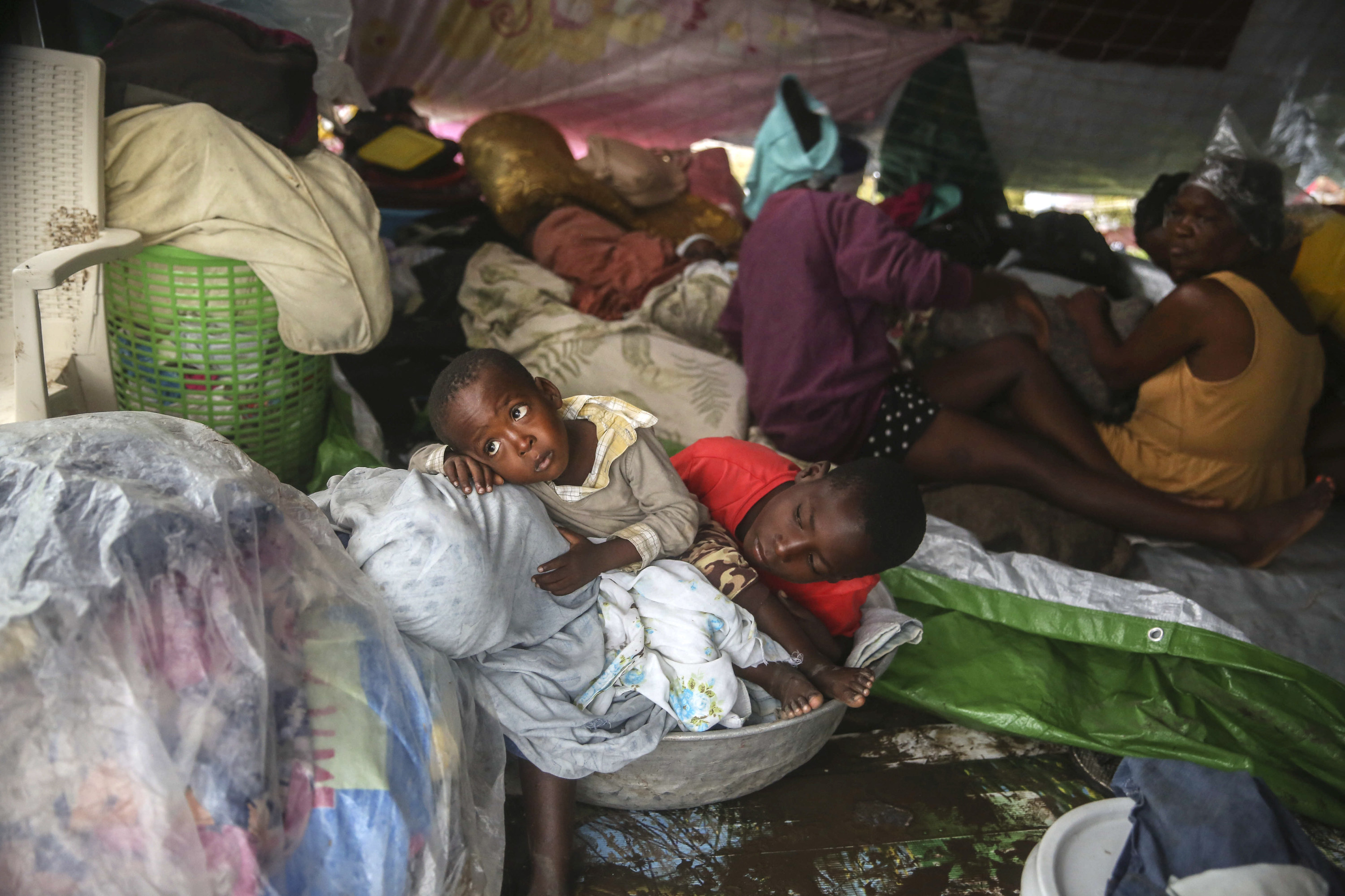 Children huddle in a basket and lie on mattresses on the ground