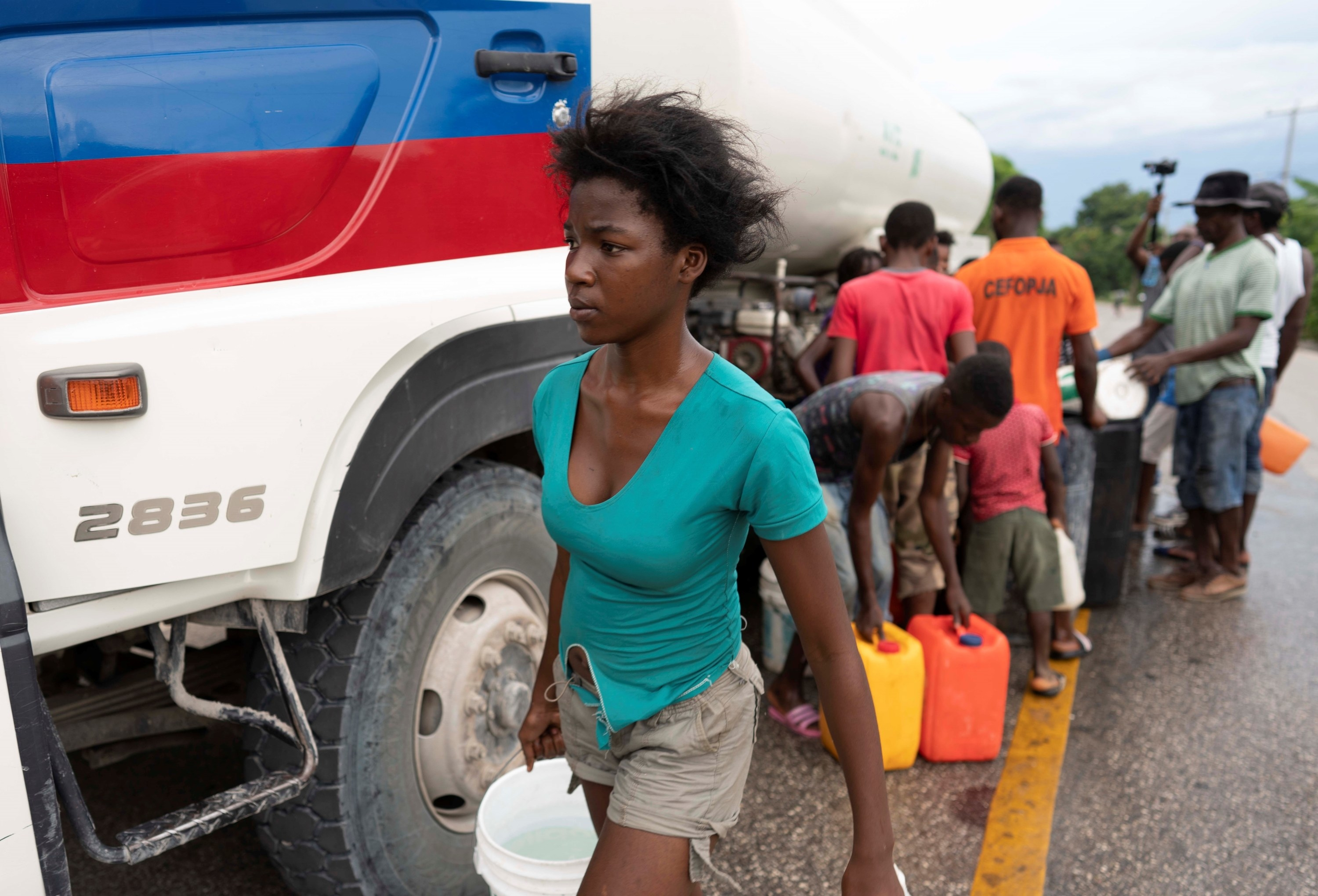 A woman walks with a bucket of water from a group of people filling up cans and buckets from a tank truck