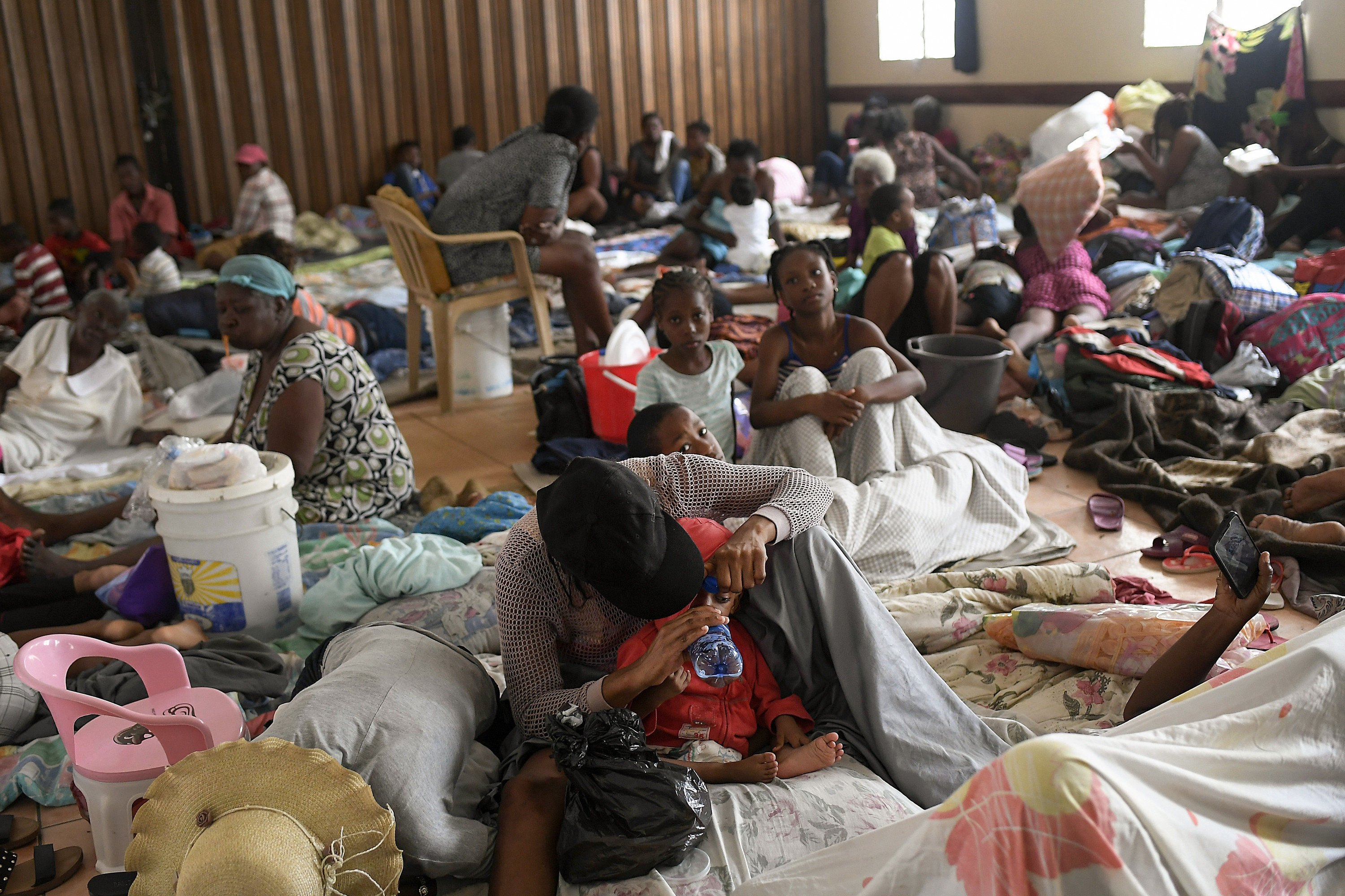 Children and families huddle together on the ground in an indoor shelter; in the foreground, an adult holds a water bottle up to a baby's mouth