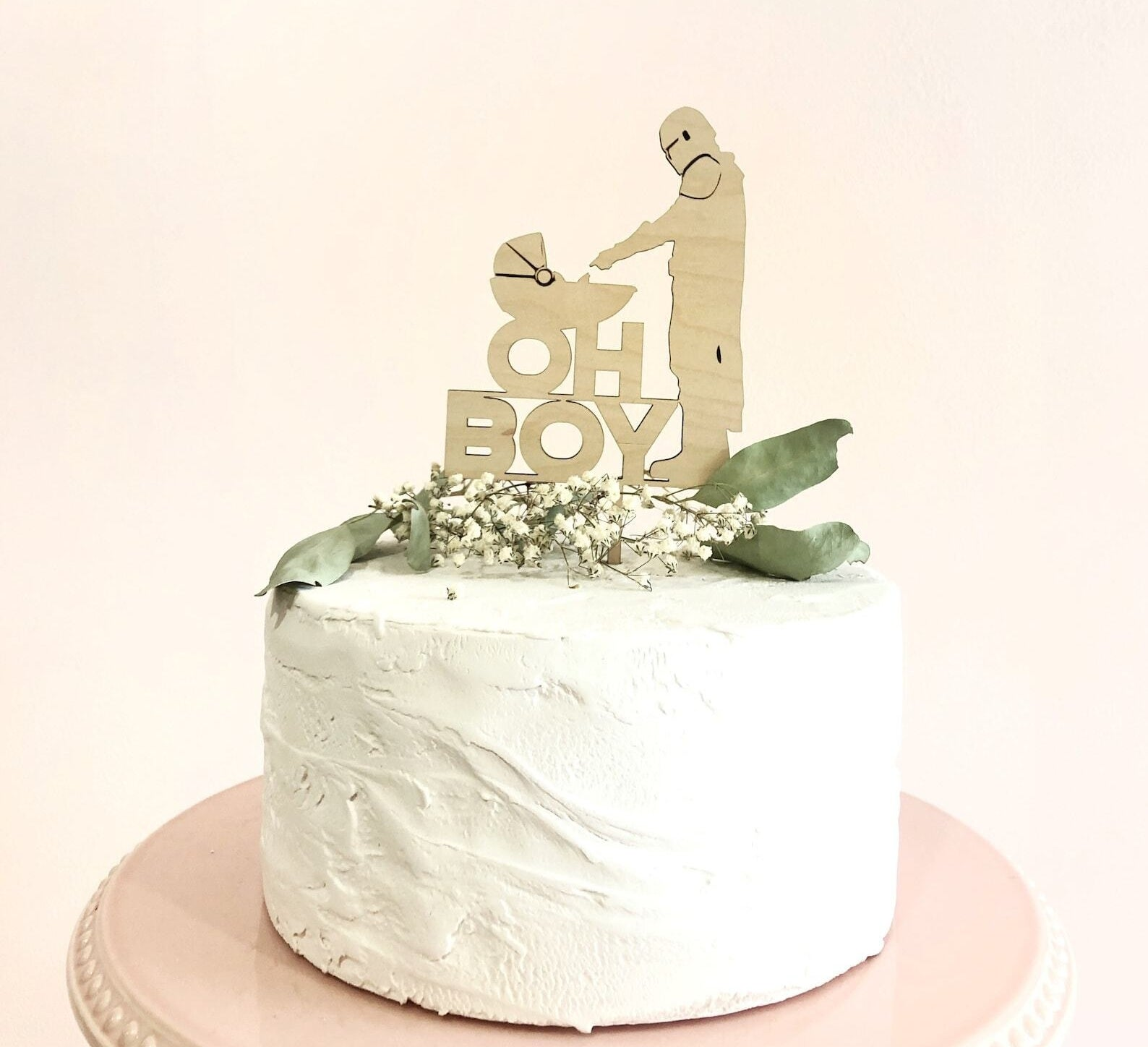 frosted cake with the child and the mandelorian cake topper that says oh boy