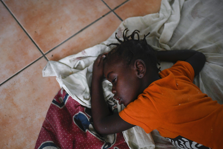 A young girl sleeps on the floor of a church