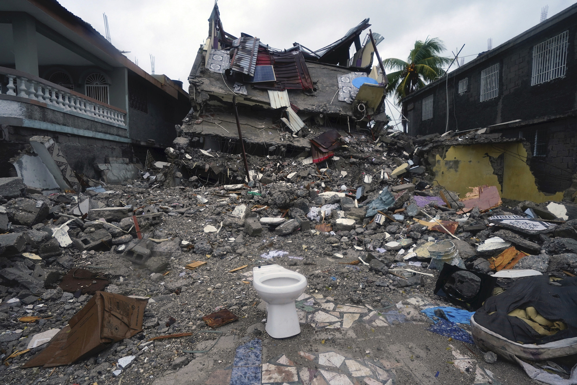 A multistory building collapsed into a pile of rubble amid debris from homes scattered all over the street
