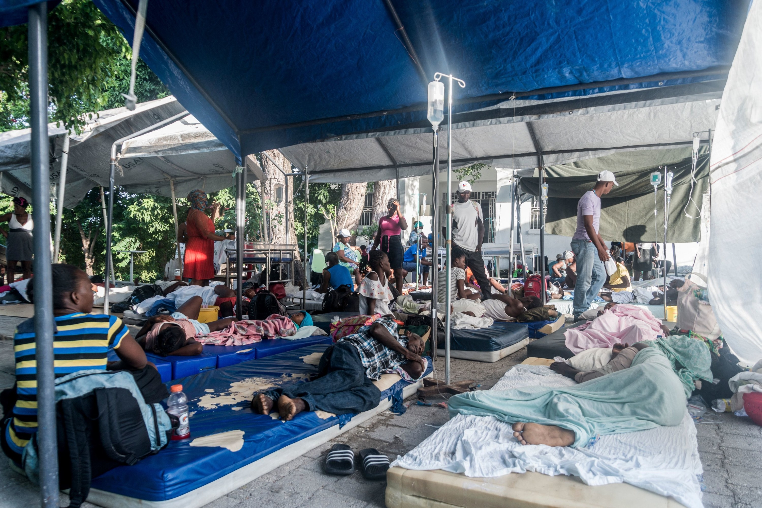 People lie on mattresses on the ground in a pop-up hospital assembled with metal rods and a tarp canopy