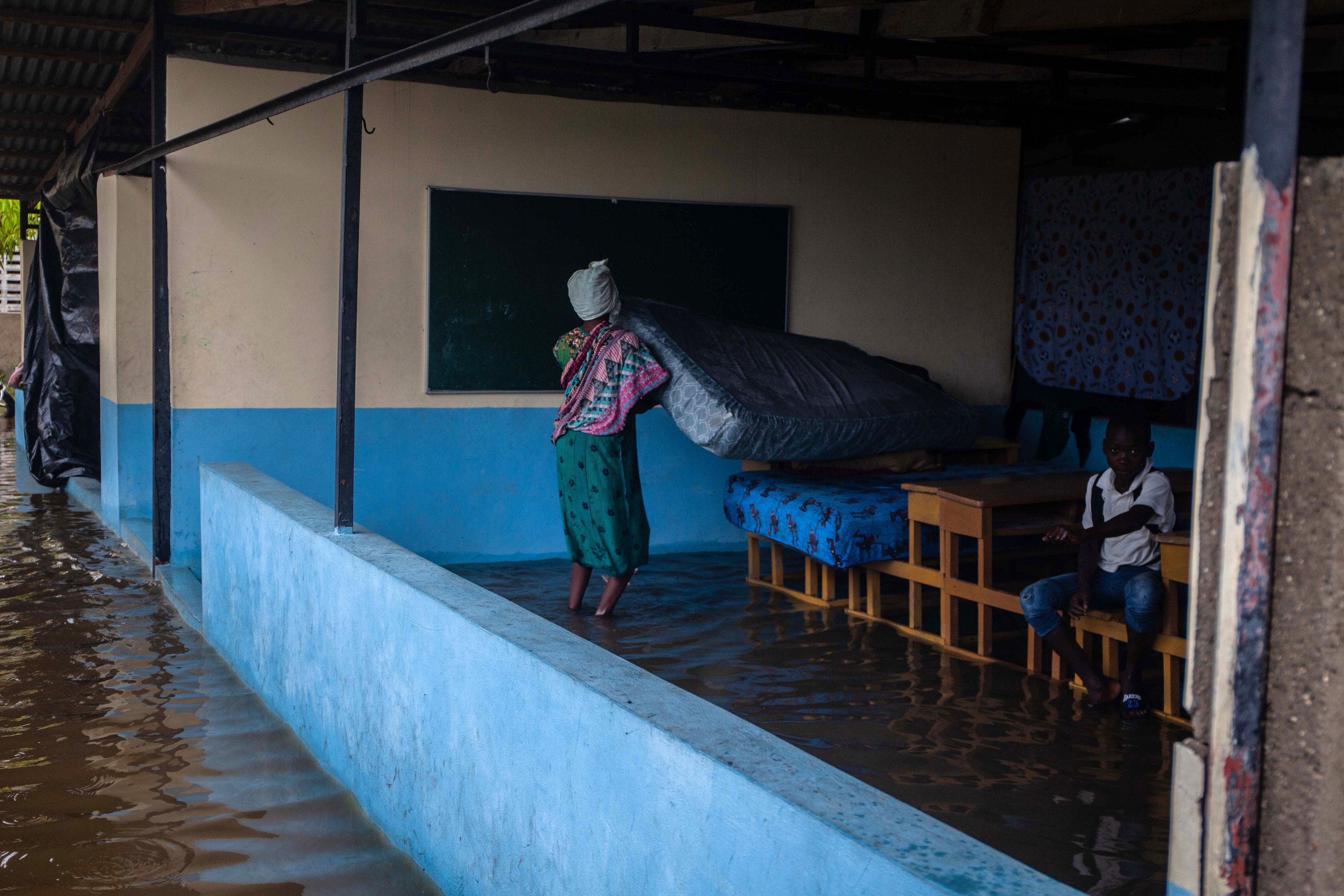 A woman is seen placing a mattress on a tabletop as she walks in ankle-high water