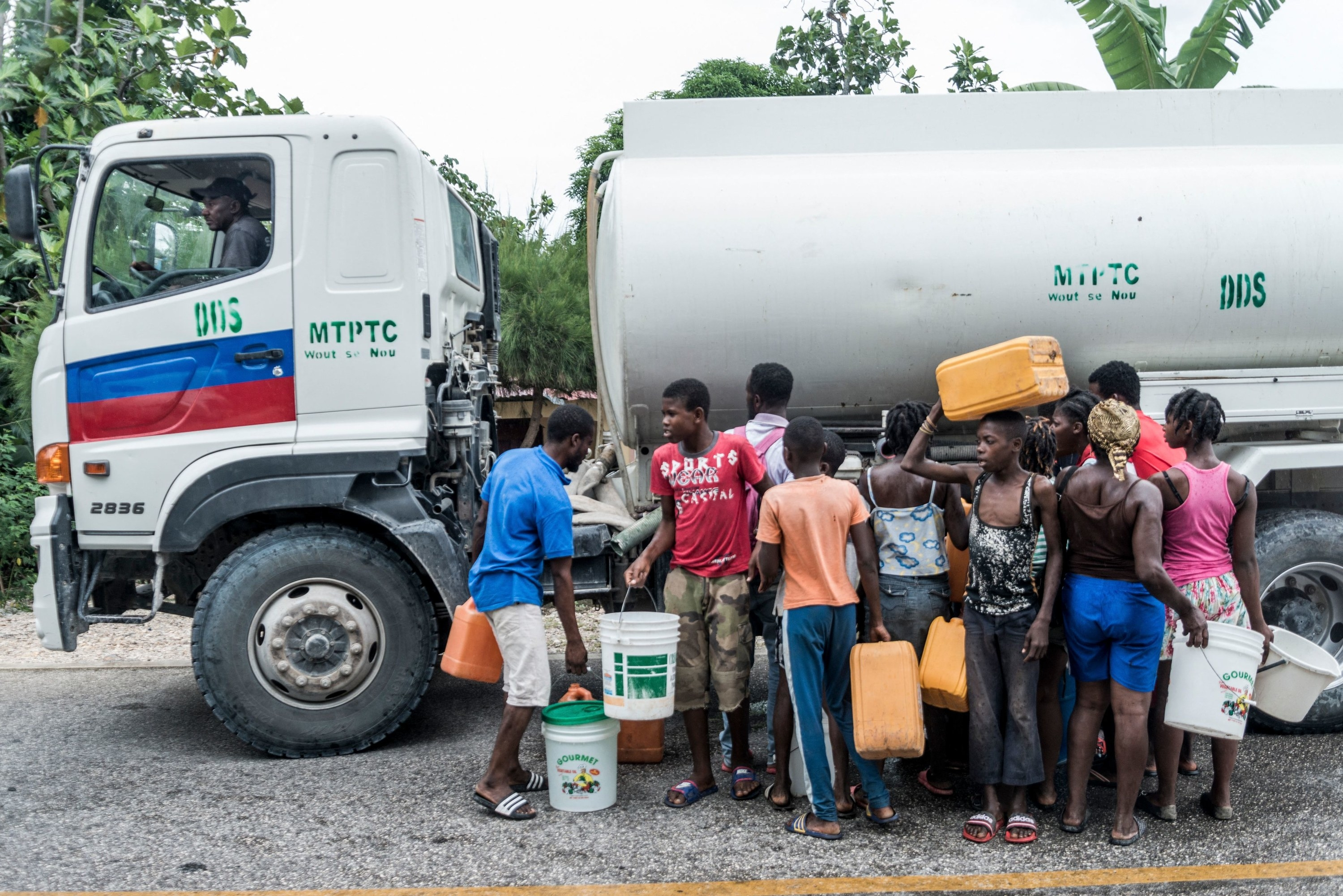 Haiti residents wait in line for water by a tank truck