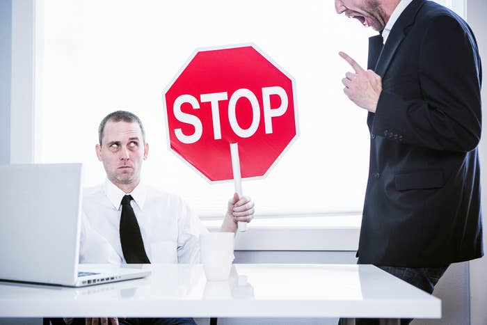 Man holding up a stop sign while his manager yells at him