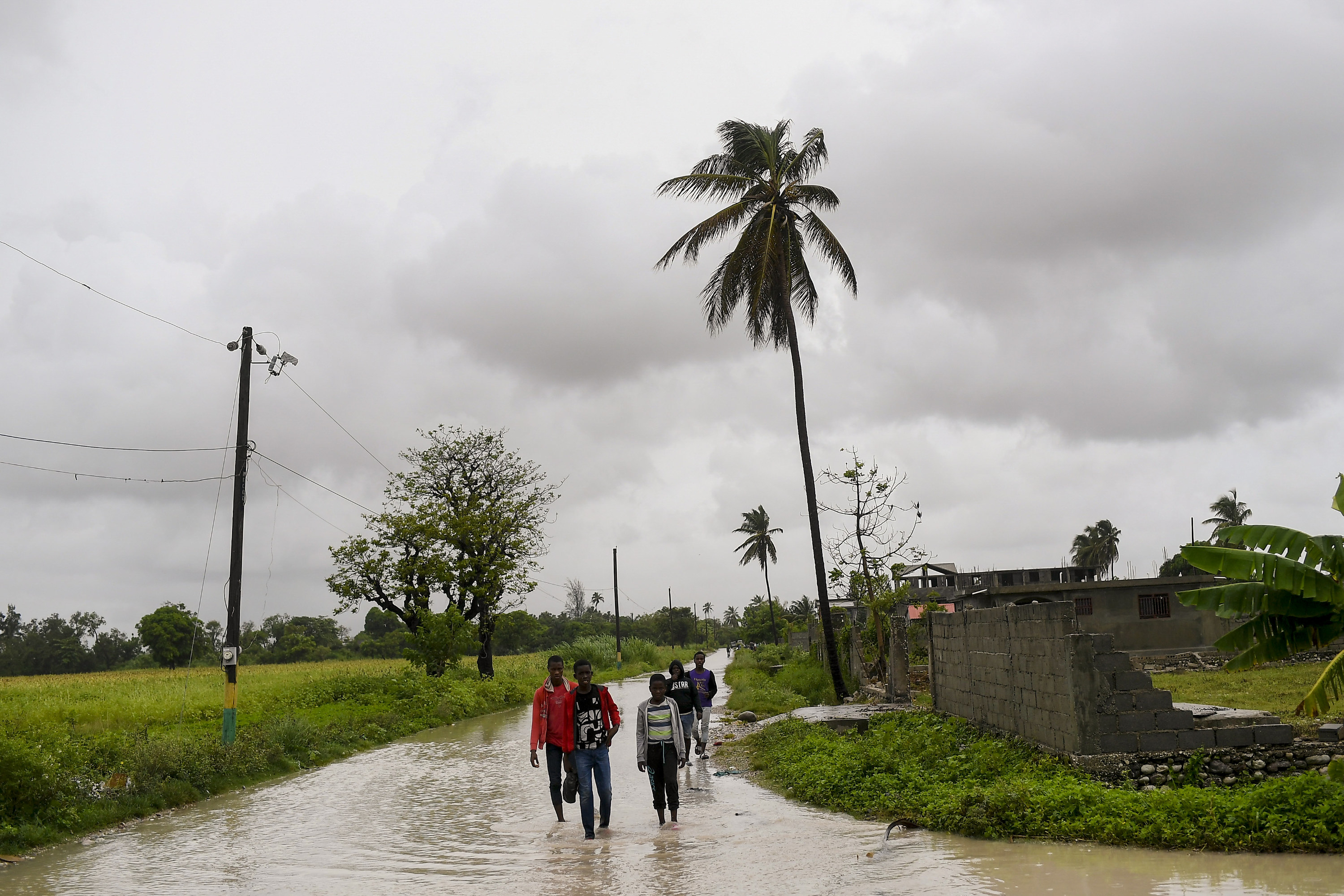 Haitian residents walk in flooded streets during a tropical storm