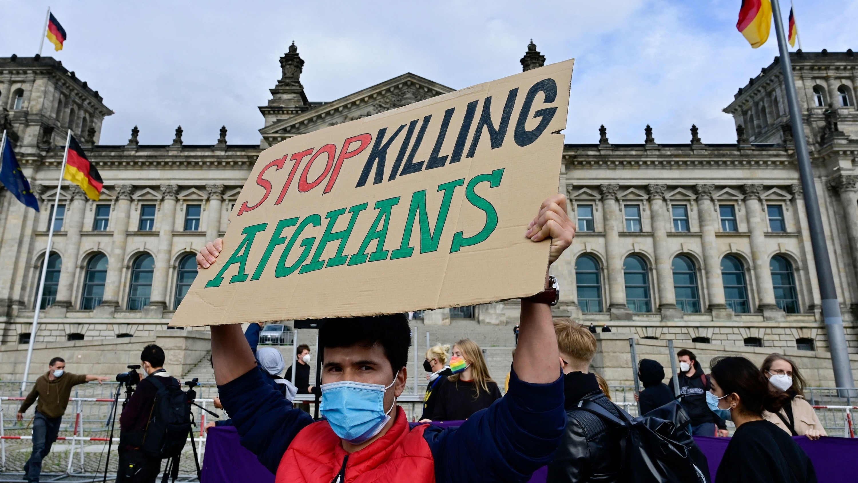 """Man holds sign reading, """"Stop killing Afghans,"""" in front of the German parliament building"""