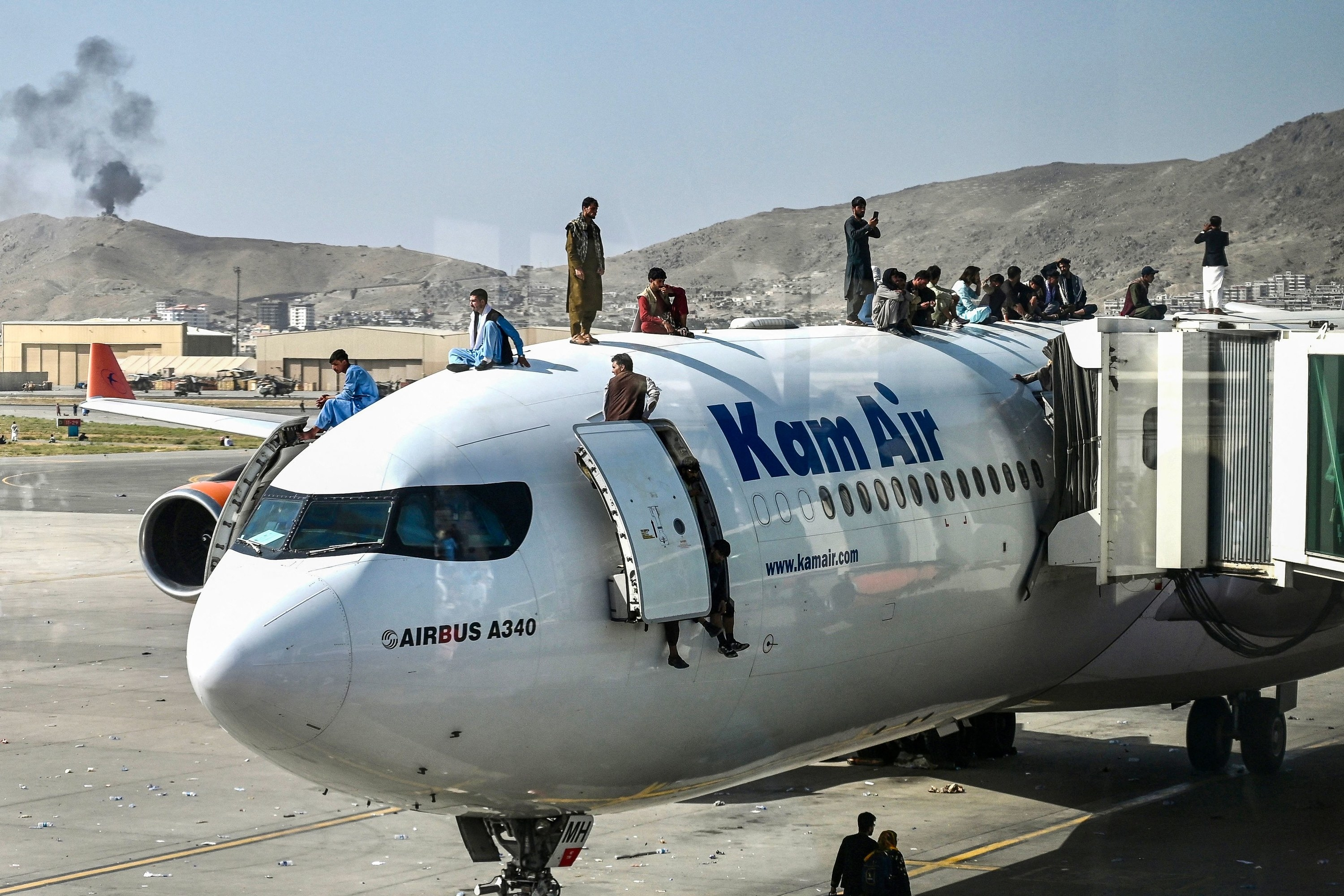 Afghan people climb atop a plane as they wait at the Kabul airport in an attempt to flee the Taliban's feared hardline brand of Islamist rule
