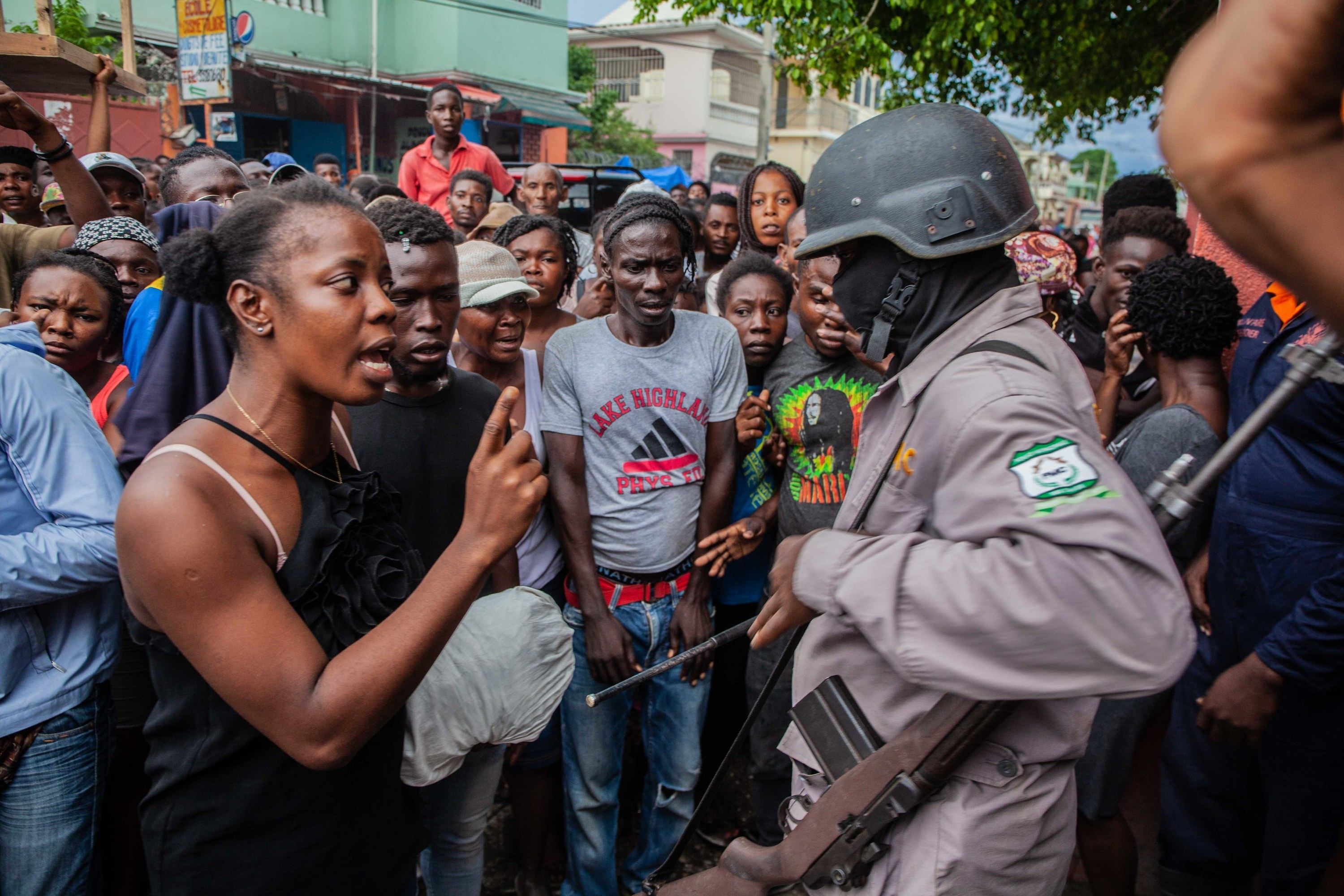 A woman confronts and points a finger at an armed soldier in front of a group of people